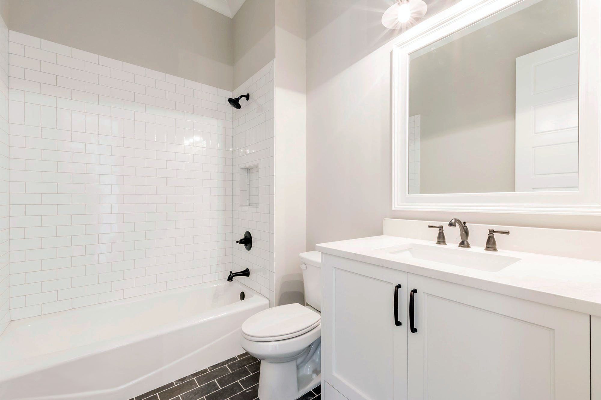 Full bathroom with a single sink vanity, elongated toilet and tub/shower combo.