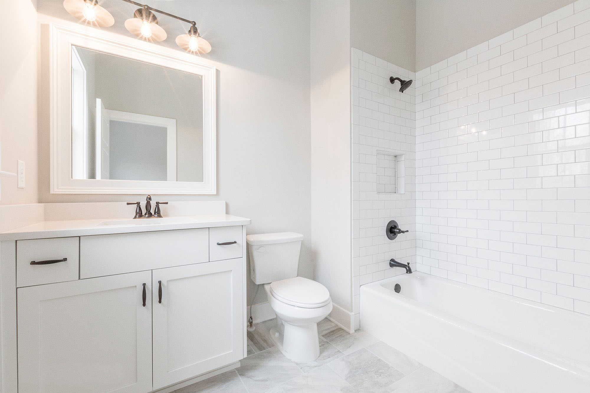 beautiful all white full bathroom with white subway tile shower, shaker style white vanity and black hardware.