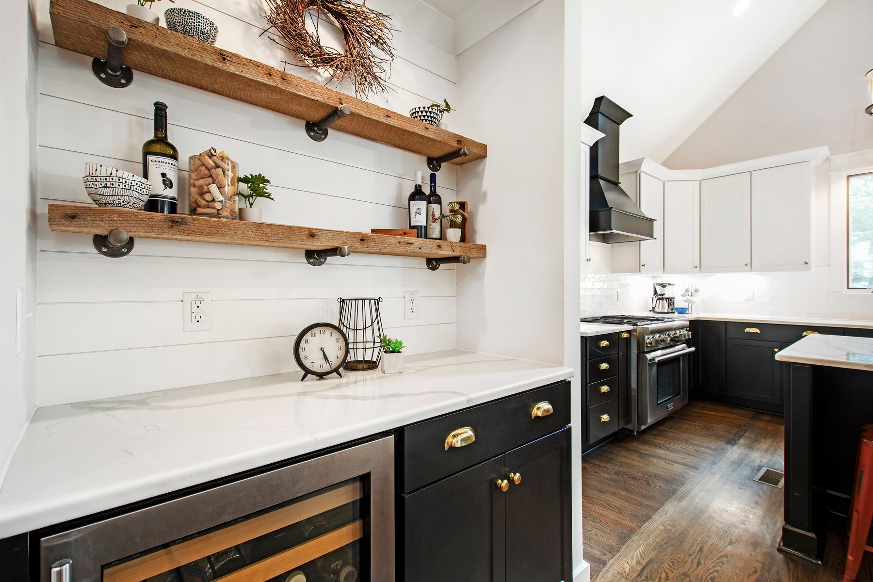 Rustic farmhouse style kitchen with black cabinets, gold hardware and white shiplap.