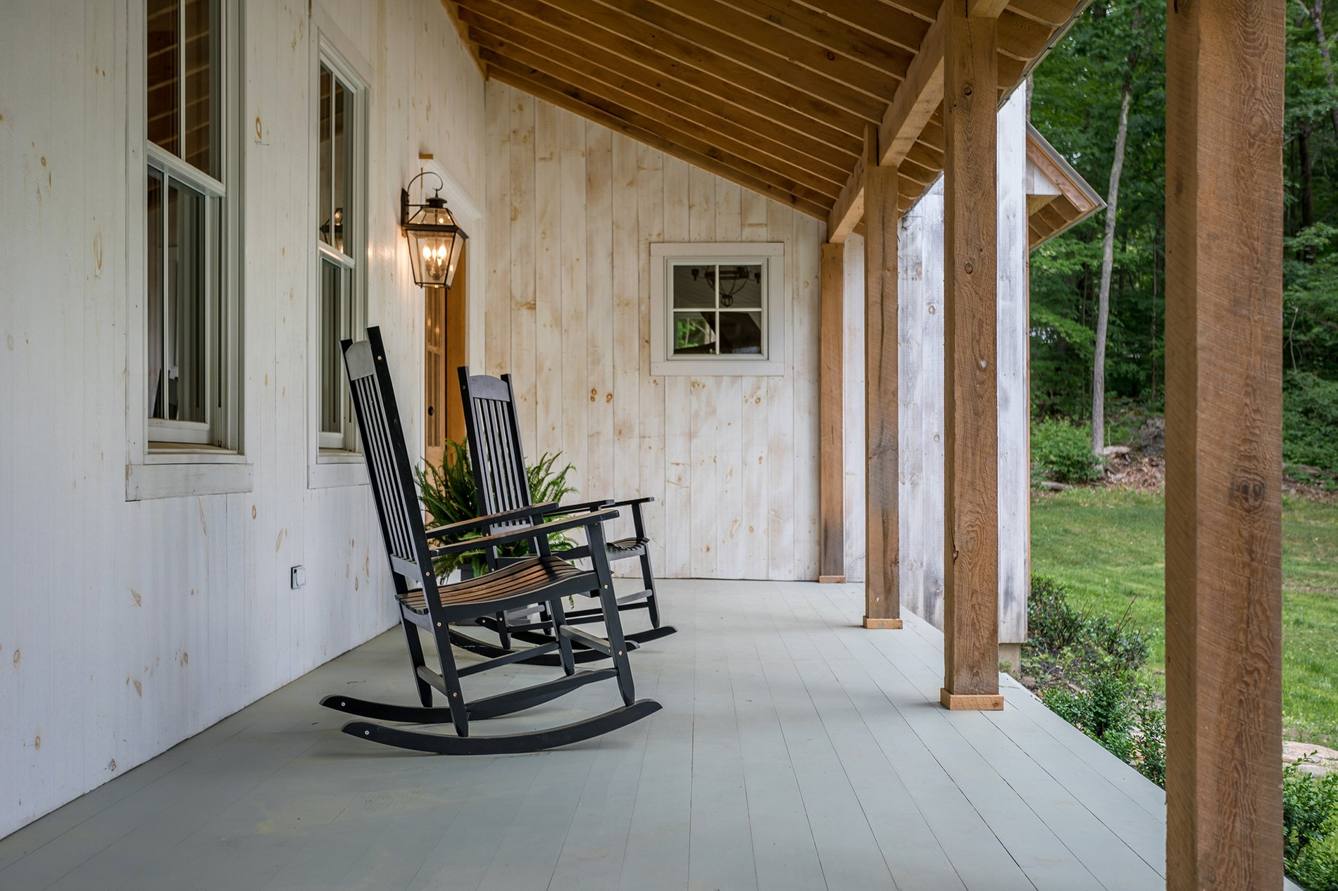 Country farmhouse style home with whitewashed wood siding along real timber exposed beams.