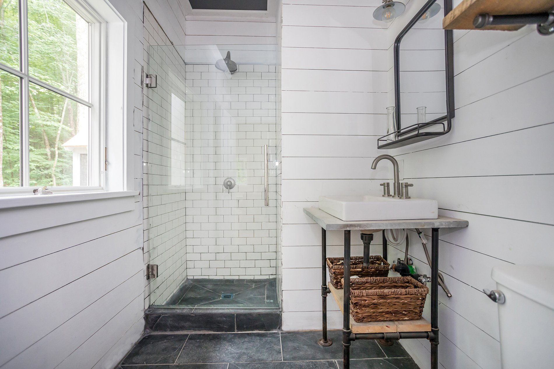 Country bathroom with white shiplap and subway shower tiles. Real wood shelving and pipe frames.