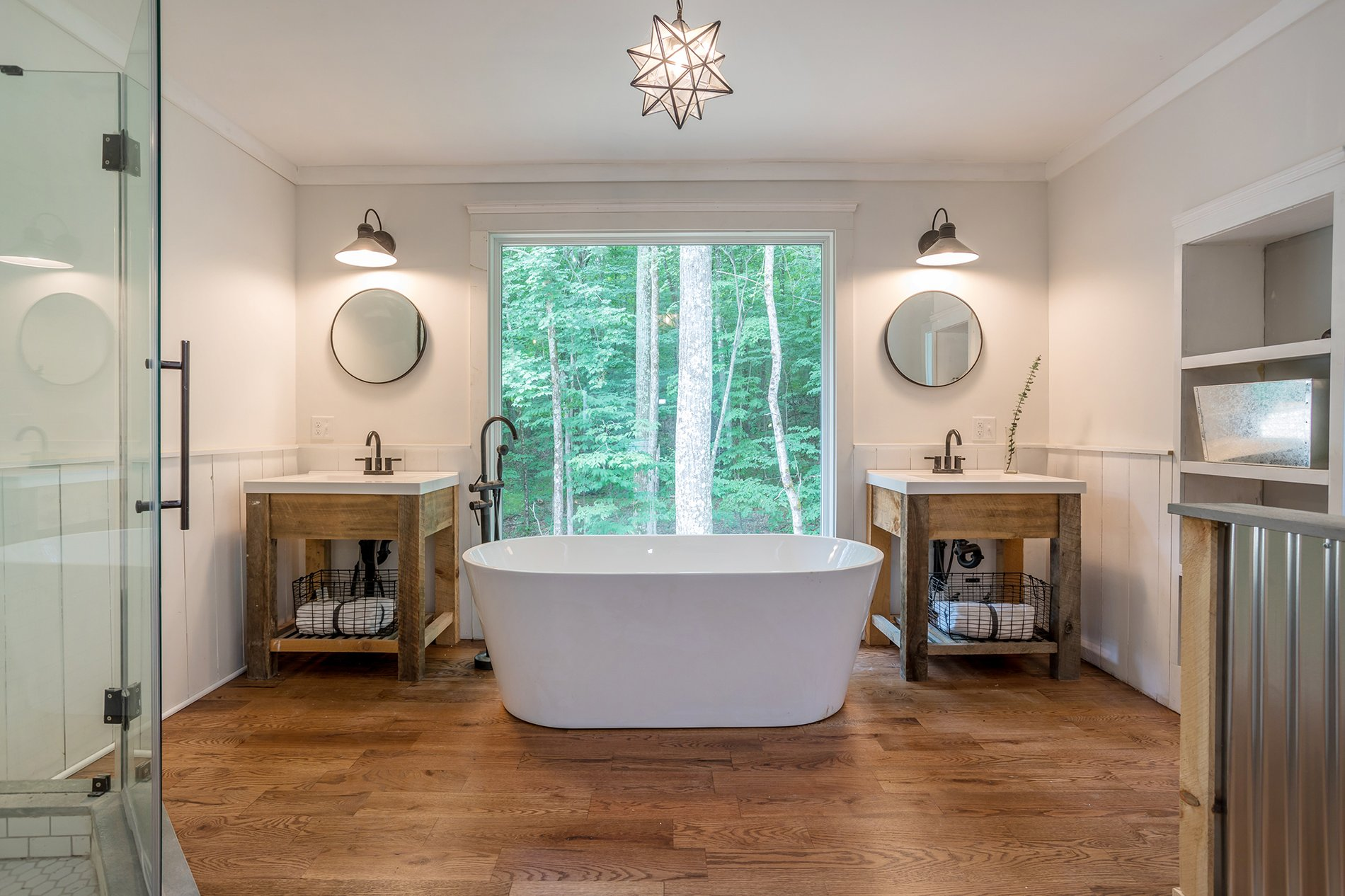 Rustic farmhouse master bathroom with a soaking tub and double sinks with custom timber bases.