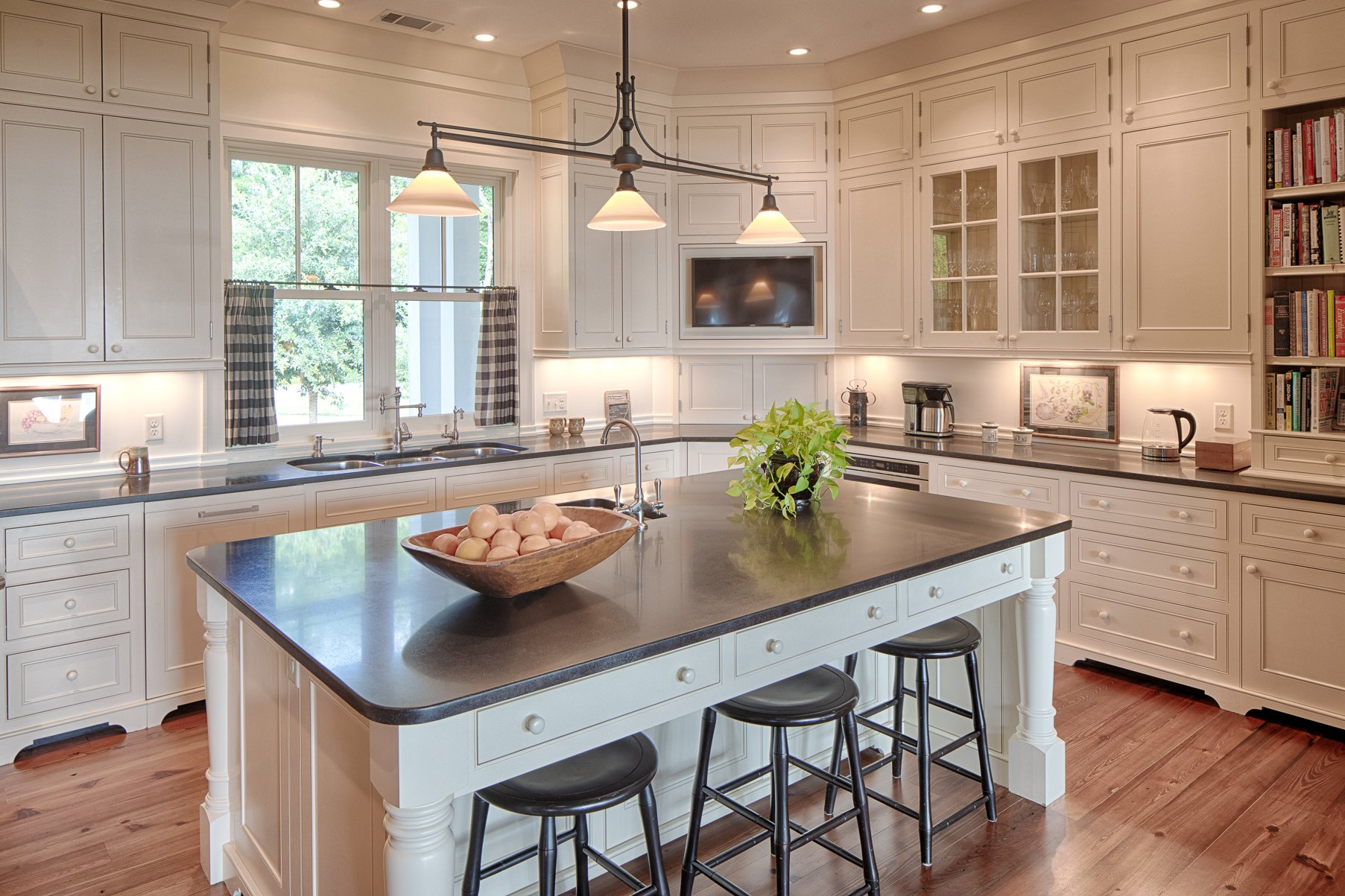 Farmhouse kitchen with white cabinets, trim, island and backsplash. Real wood floors and dark granite countertops.
