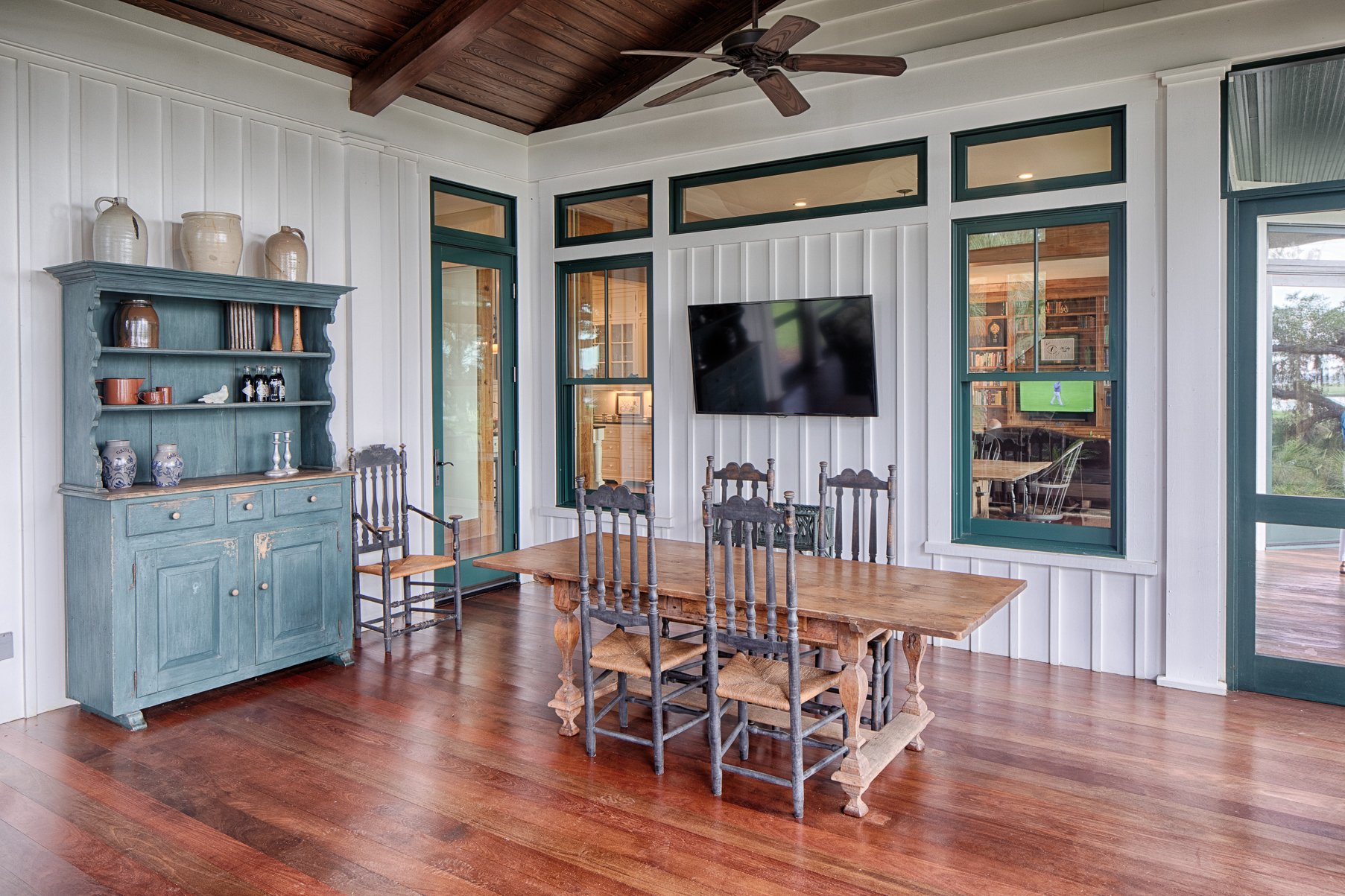 Farmhouse dining room with white board and batten style walls and blue trim.