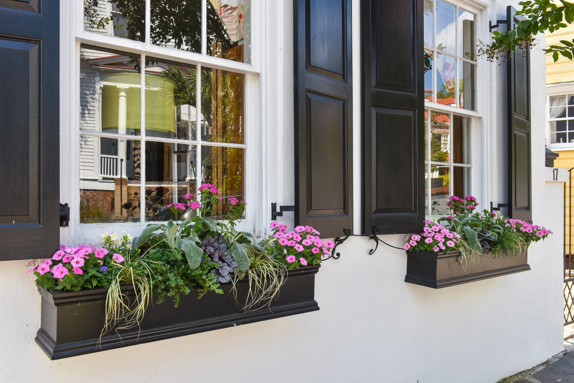 Country farmhouse with stucco siding painted solid white. Black shutters and window flower boxes.