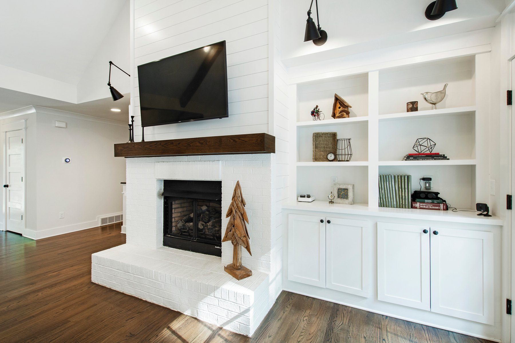 red brick fireplace painted white with built in cabinets, wood mantle and wood floors Farmhouse style
