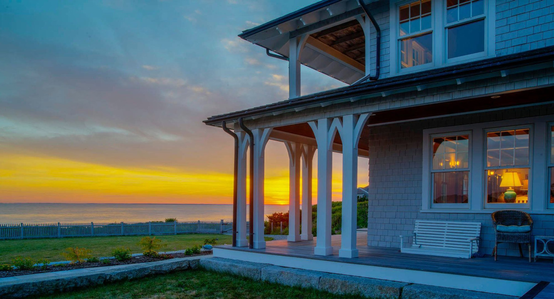 custom oceanfront home at dusk view of the back porch