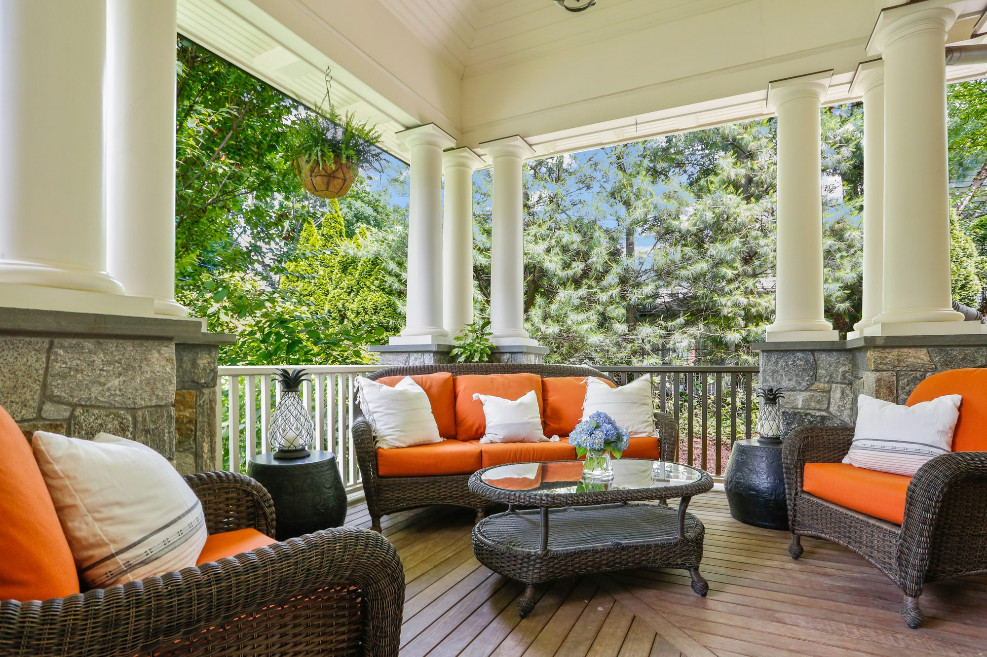 Outdoor wicker furniture with orange cushions decorated with white indoor pillows.
