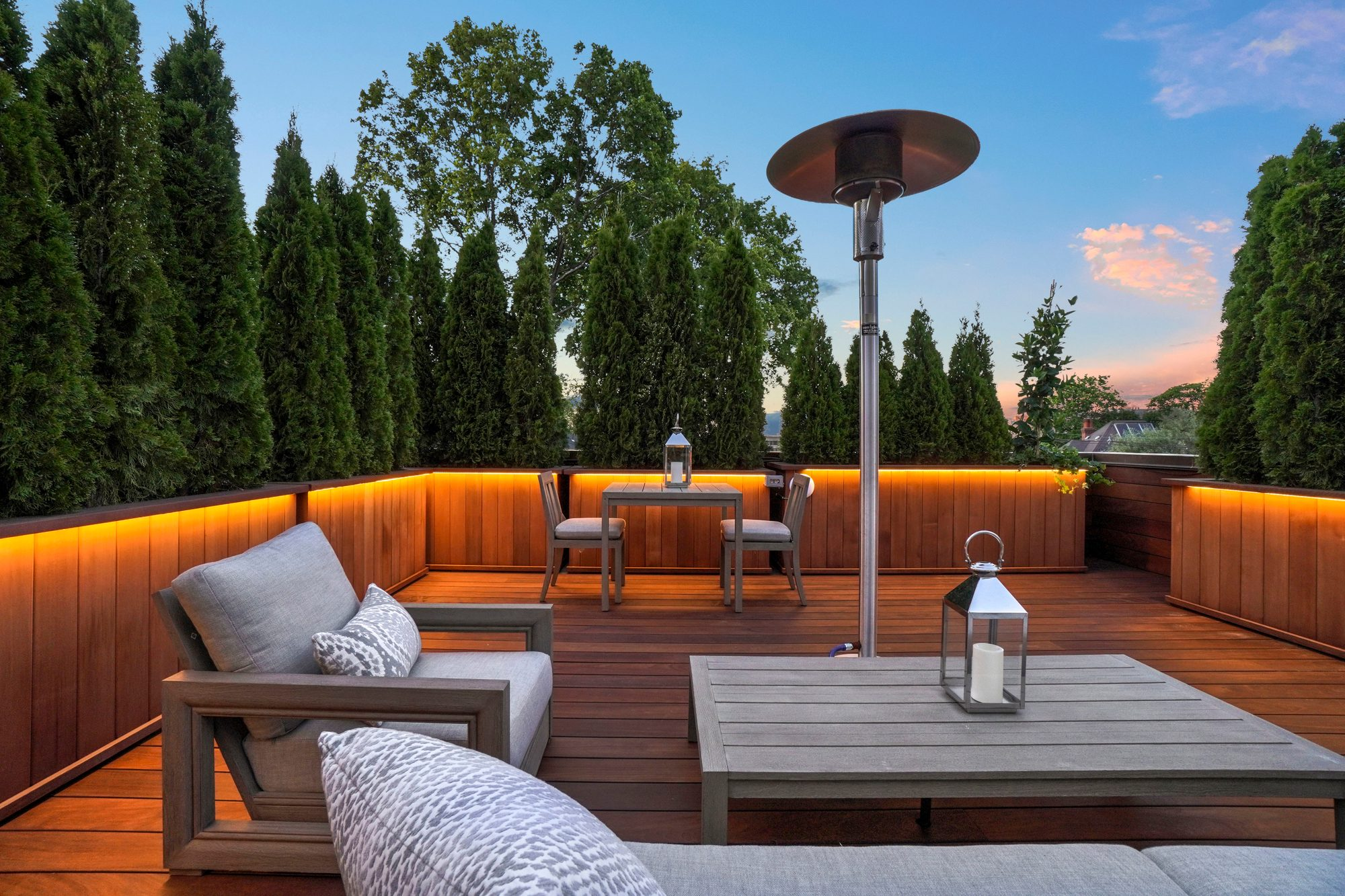 Rooftop deck with an outdoor patio set and indoor pillows.
