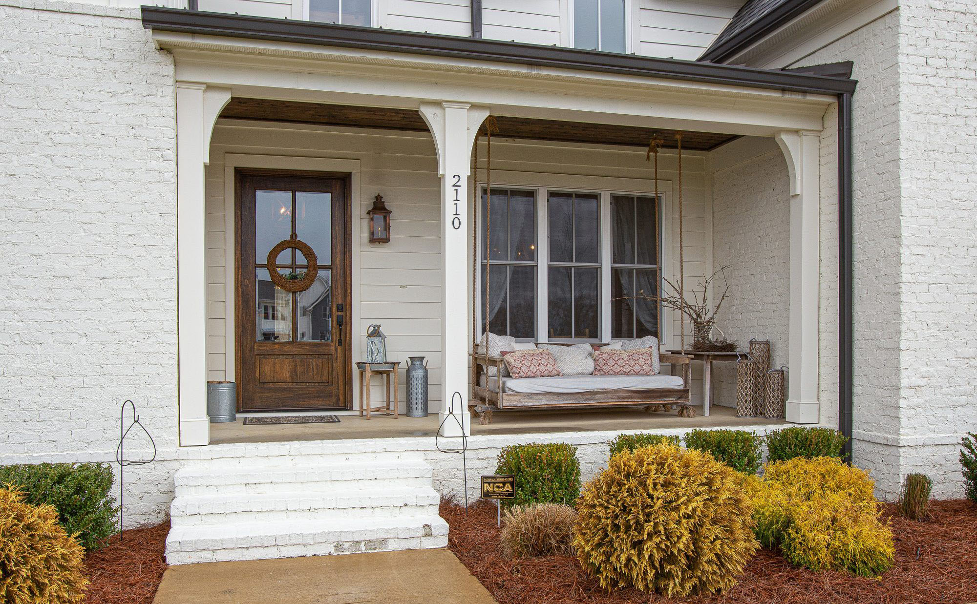 Closeup view of a brick home painted white. Country front porch with a real wood front door, wood ceiling and a wood bench swing.