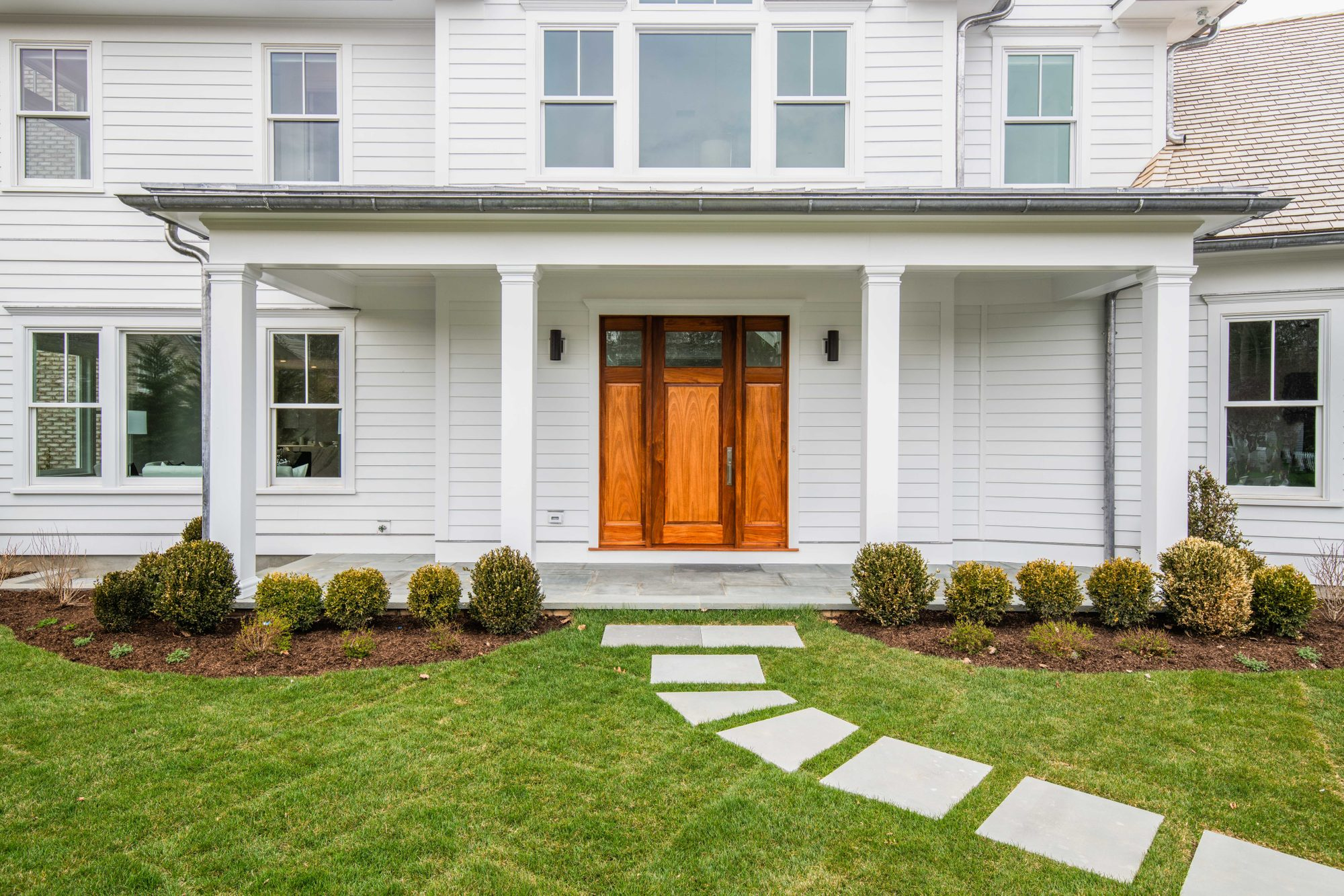 Covered front porch with a blue stone paver floor. White siding & columns with a natural stained front door.