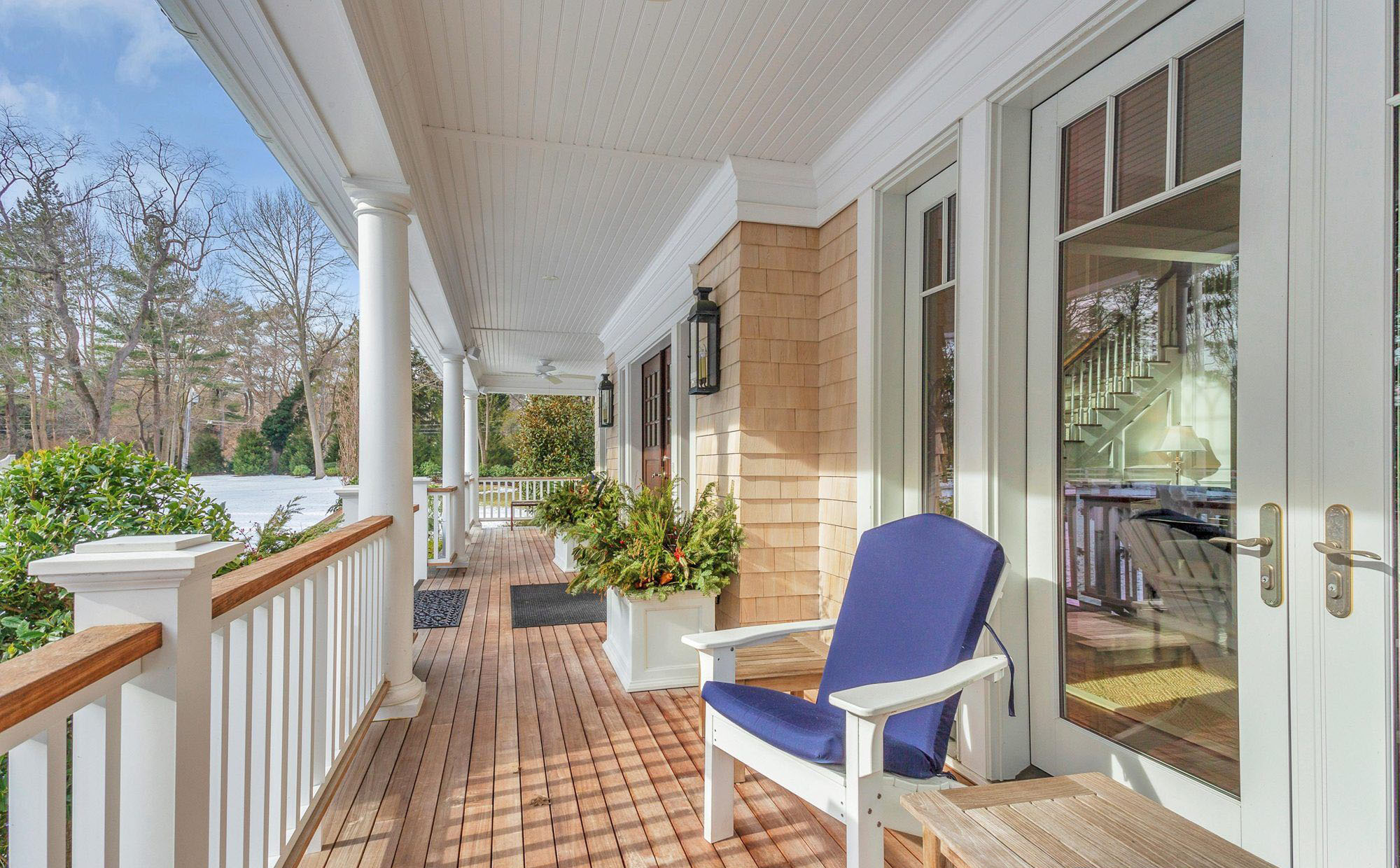Natural real wood front porch floor with white columns & railings. Cedar shake siding.