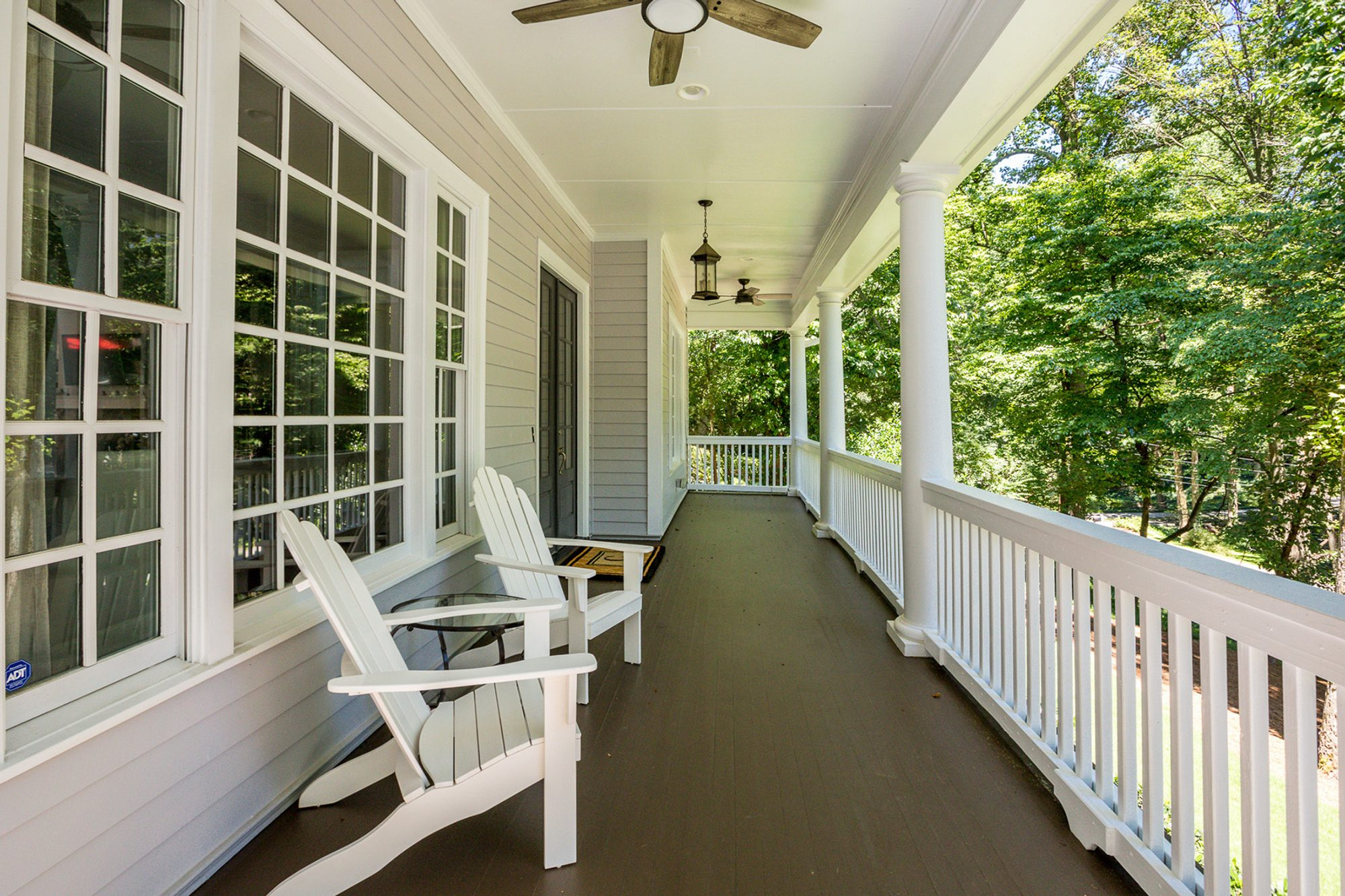 Covered porch with wood flooring painted black. Gray siding, white trim, rails & columns with a black front door.