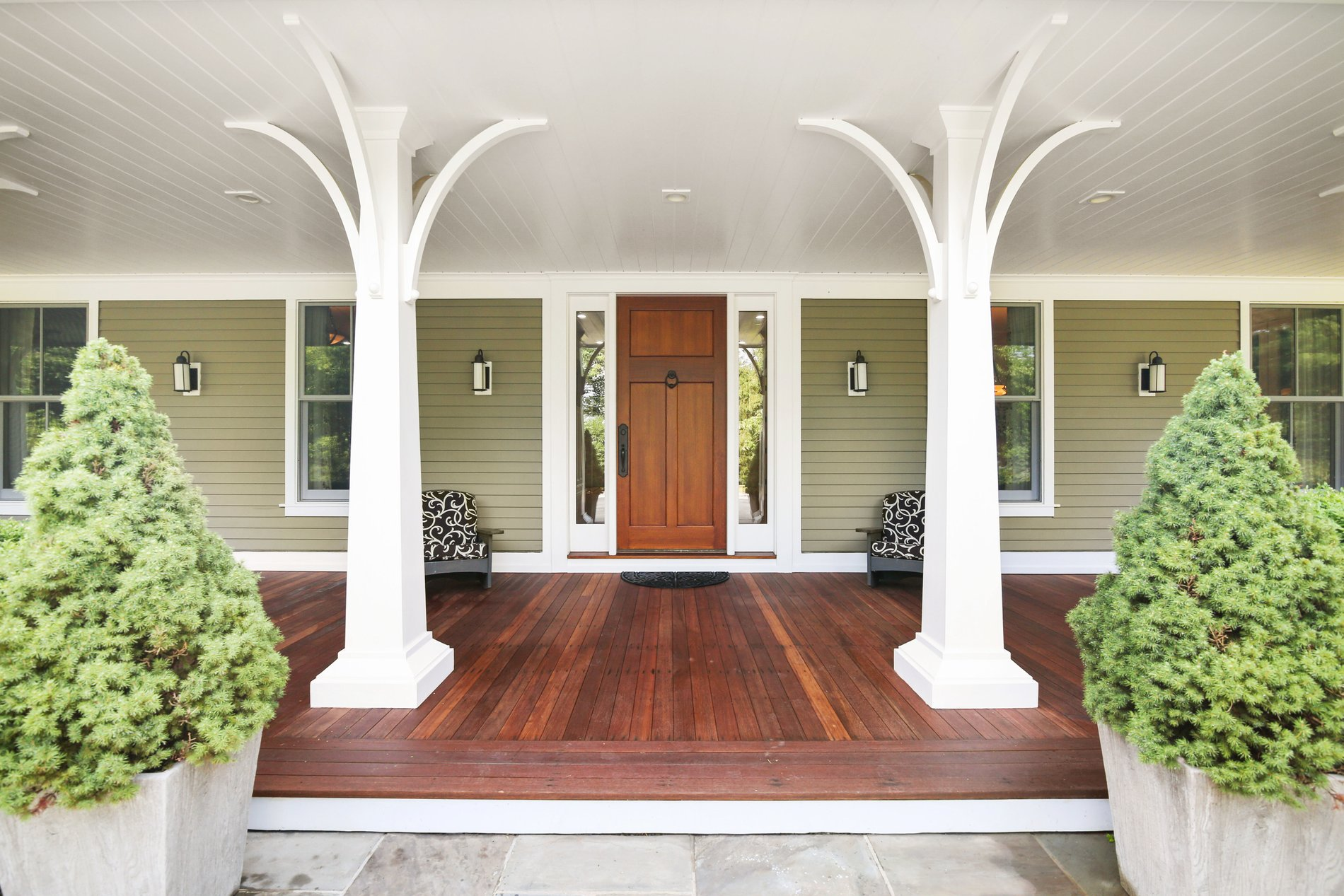 Covered front porch with stained wood flooring.