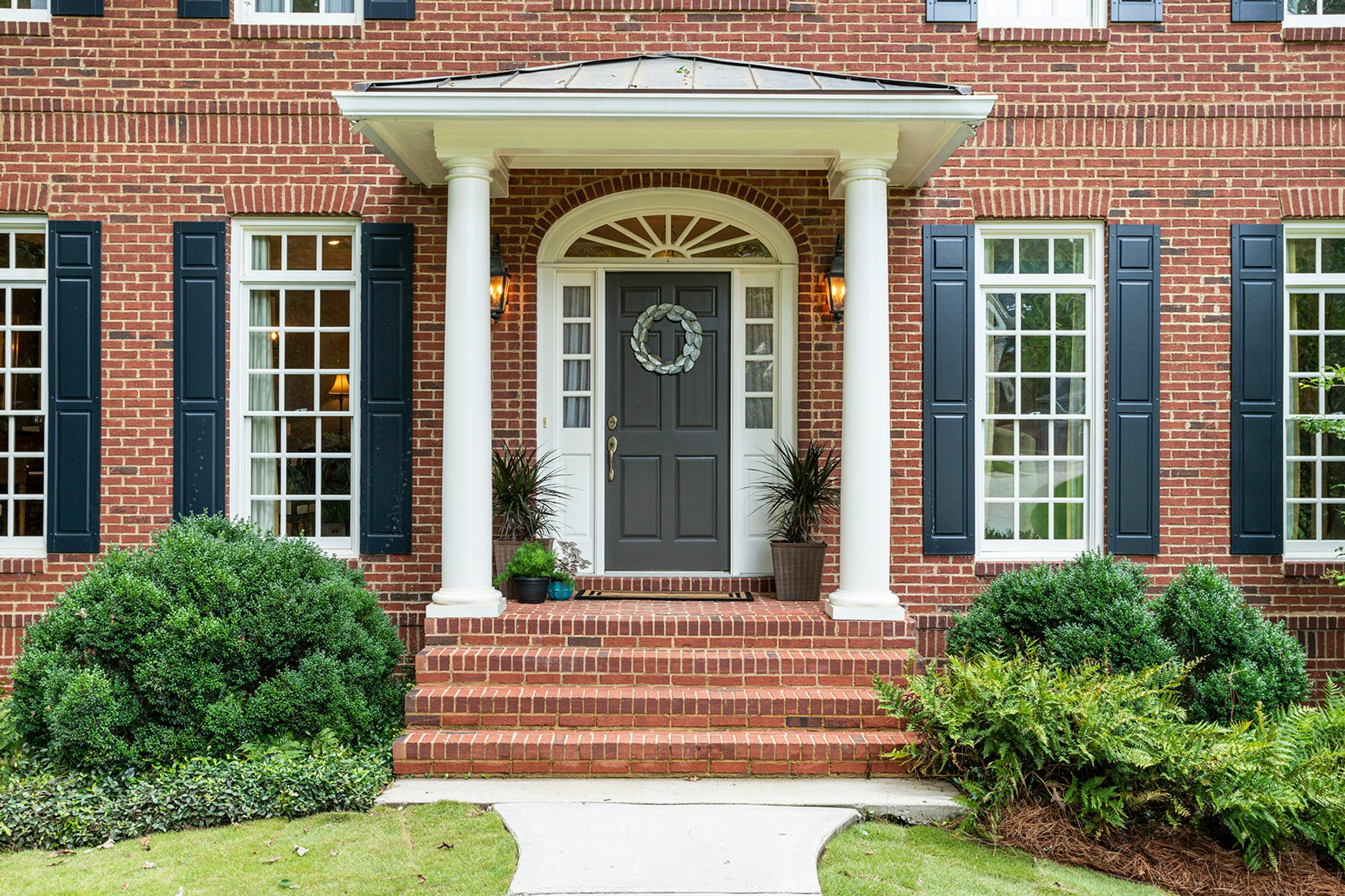 Red brick front porch with brick flooring and matching red brick walls.