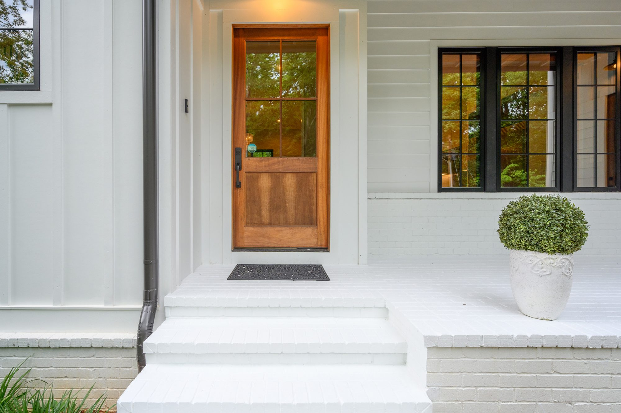 Front porch built from red brick and painted white on a Modern style farmhouse.