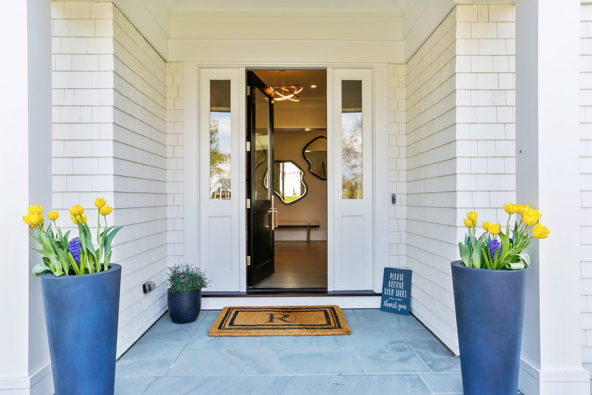 Blue stone front porch floor with white siding and a black front door.