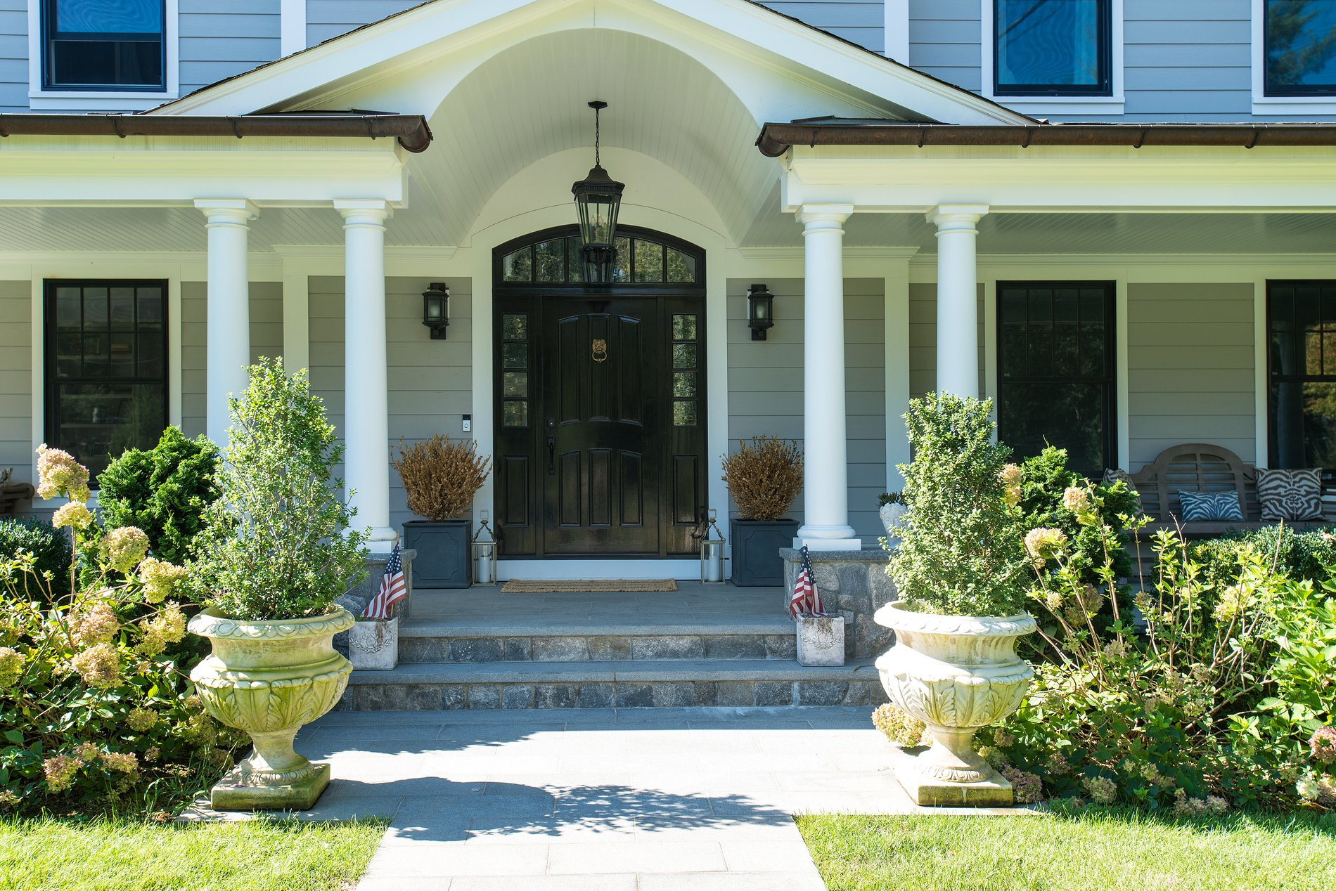 Covered porch with a blue stone paver floor. Gray siding, white trim and a black front door.