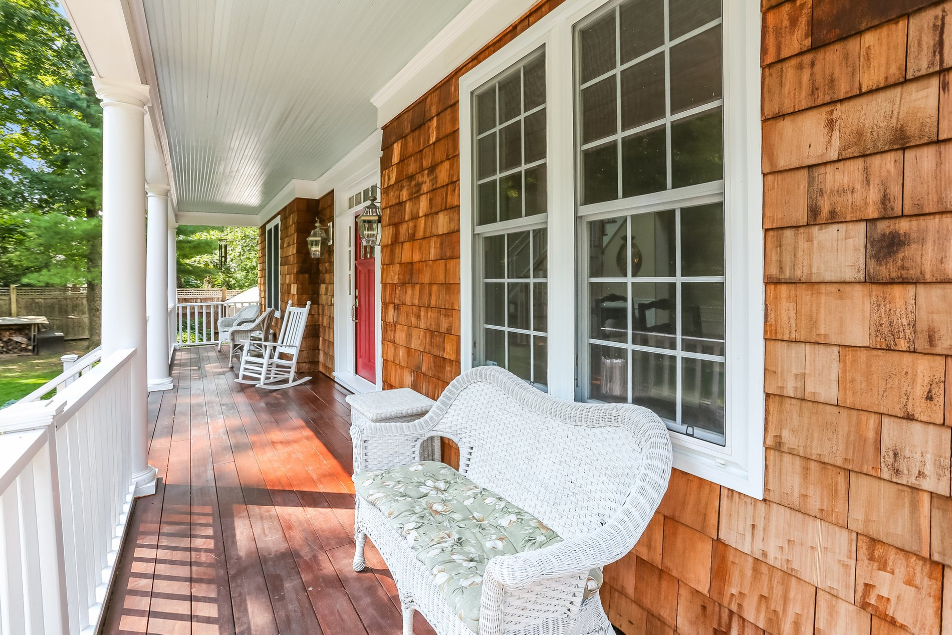 Real wood front porch floor with a light brown natural stain, white columns and cedar shake siding.