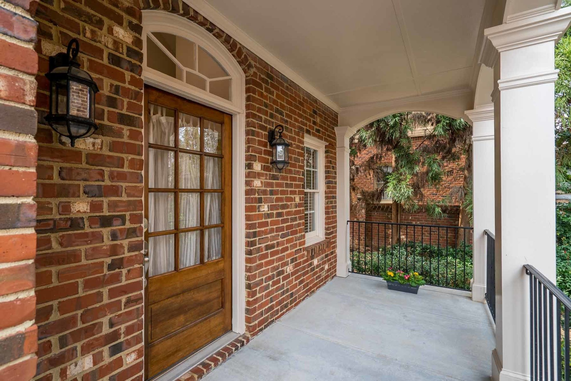 Covered front porch with a concrete floor. red brick walls. square columns with black iron railings.