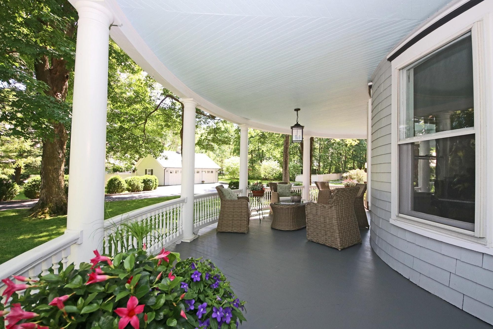 Covered wrap around wood porch flooring painted solid gray.