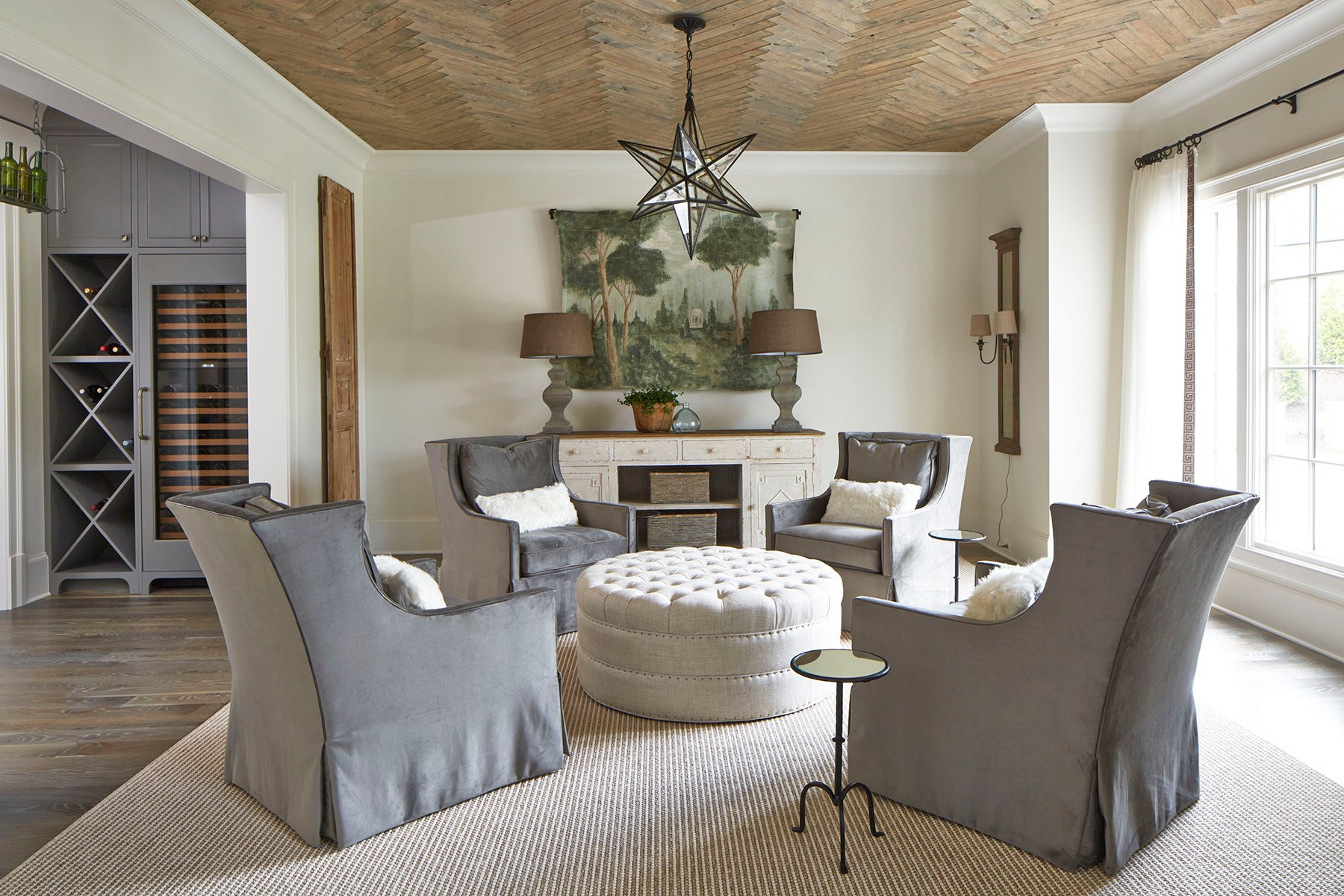 Living room with 4 plush grey chairs over a tan woven fiber rug and cream colored ottoman.