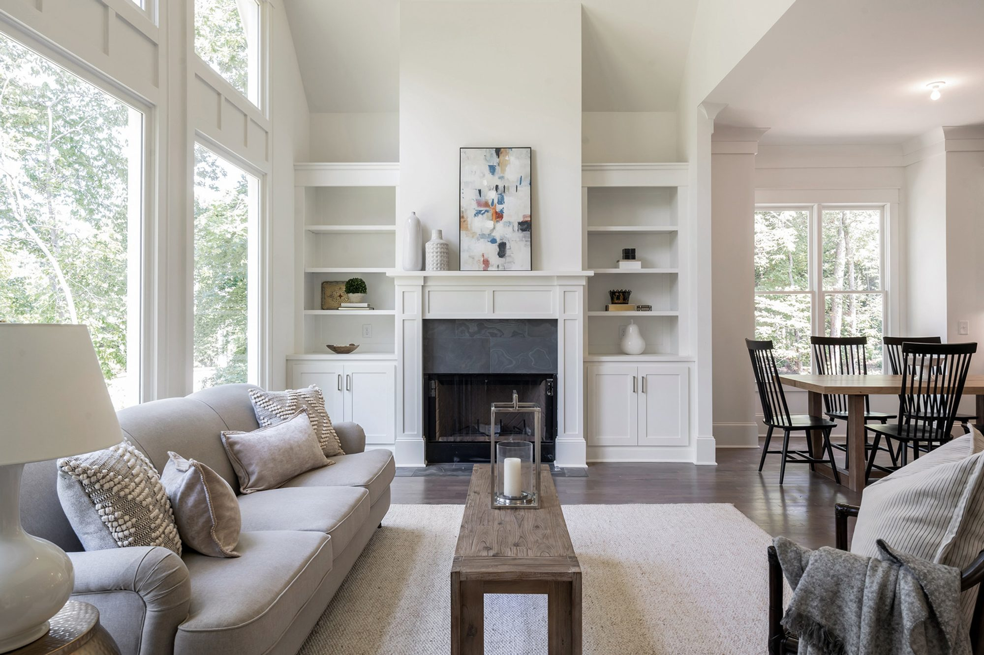 Grey sofa paired with a natural fiber woven area rug with wood floors and furniture.