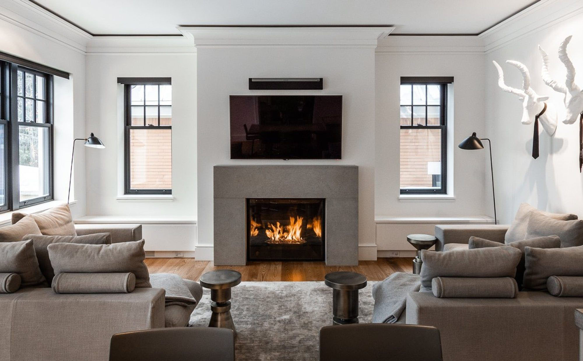 Beautiful modern style living room with warm grey sofas and matching grey area rug in front of a gas fireplace.