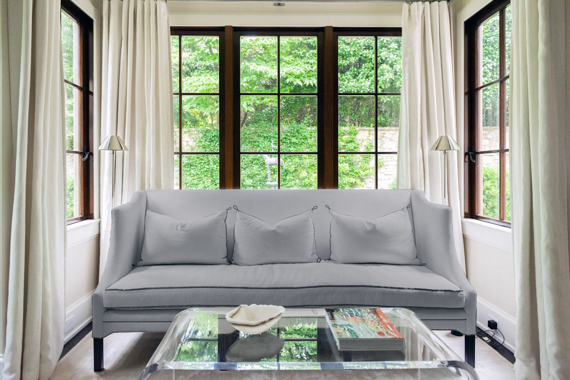 Light grey couch with a cream colored thin composite fiber rug.