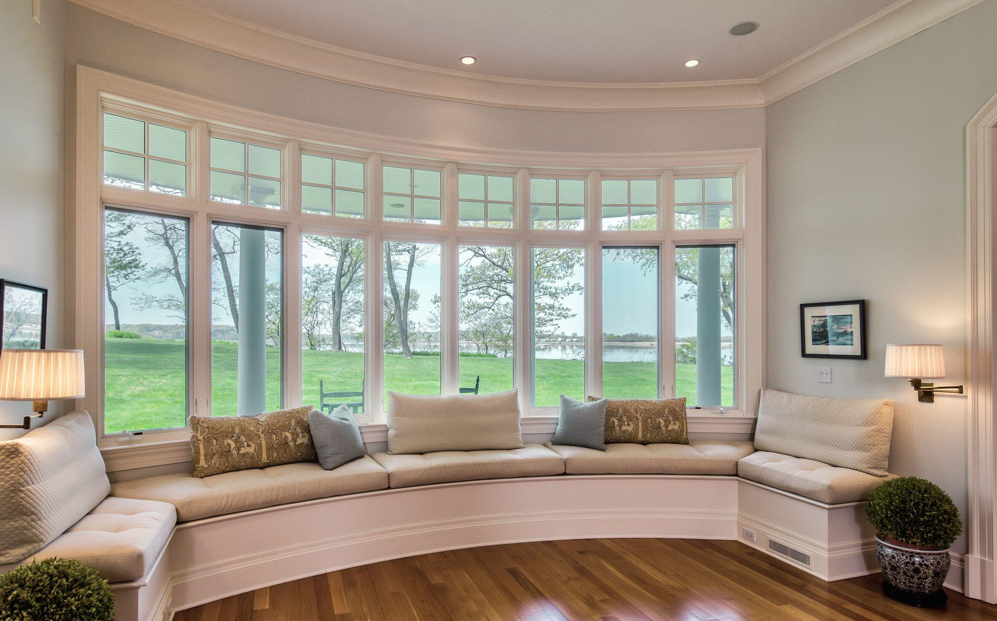 Round window seat with tan cushions and lots of pillows.