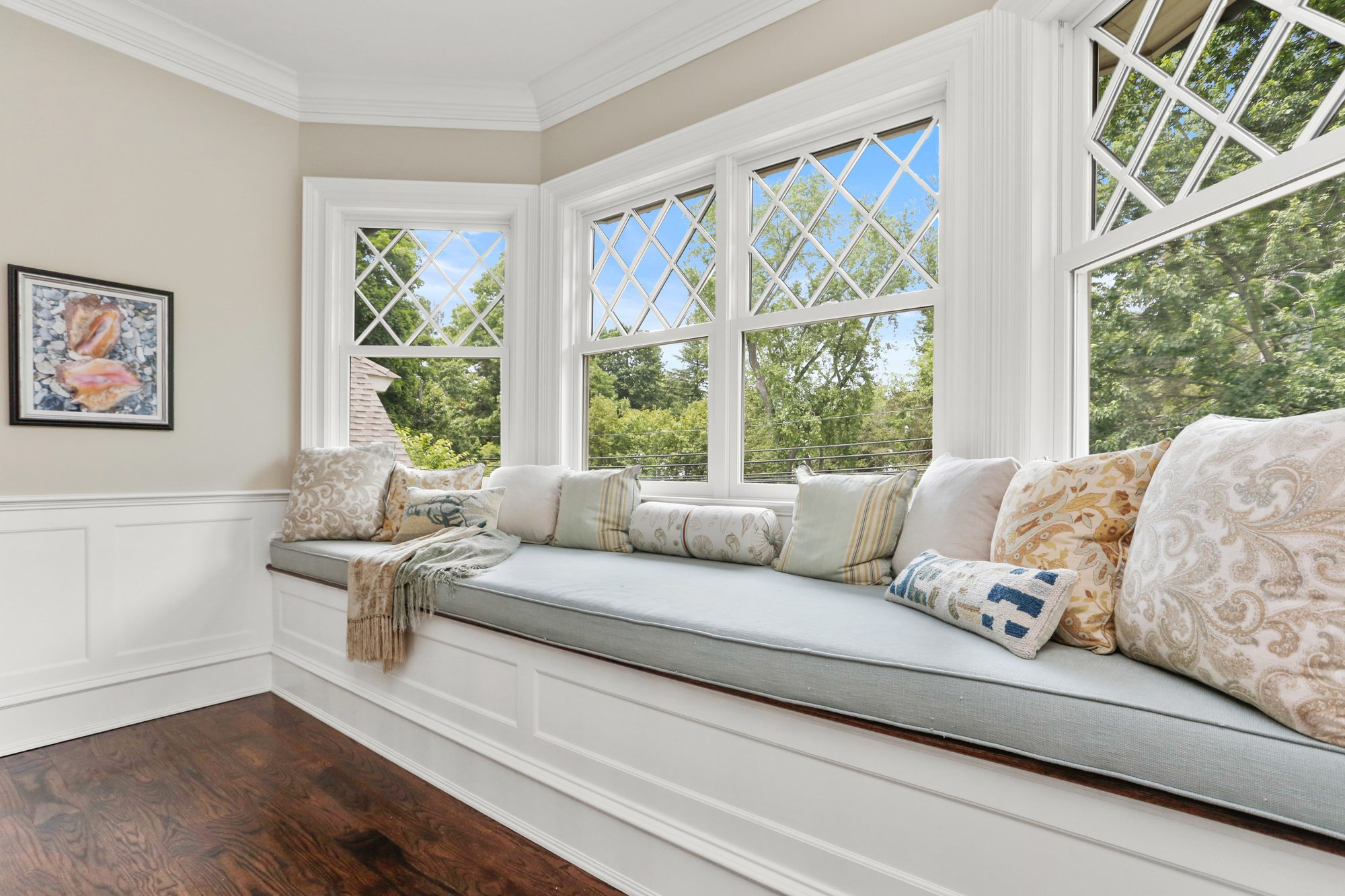 Large bay window with a window seat featuring a 4 inch cushion and lots of pillows.