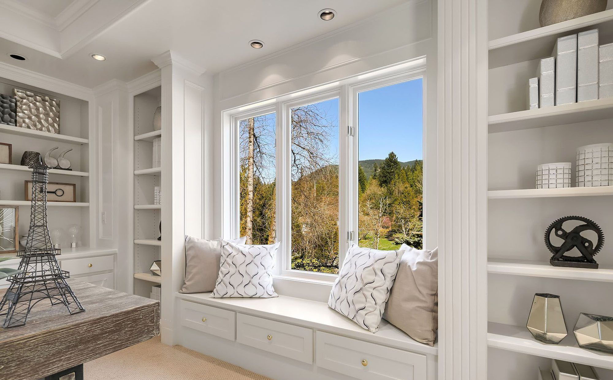 Monochromatic home office with a window seat featuring pull out drawers.