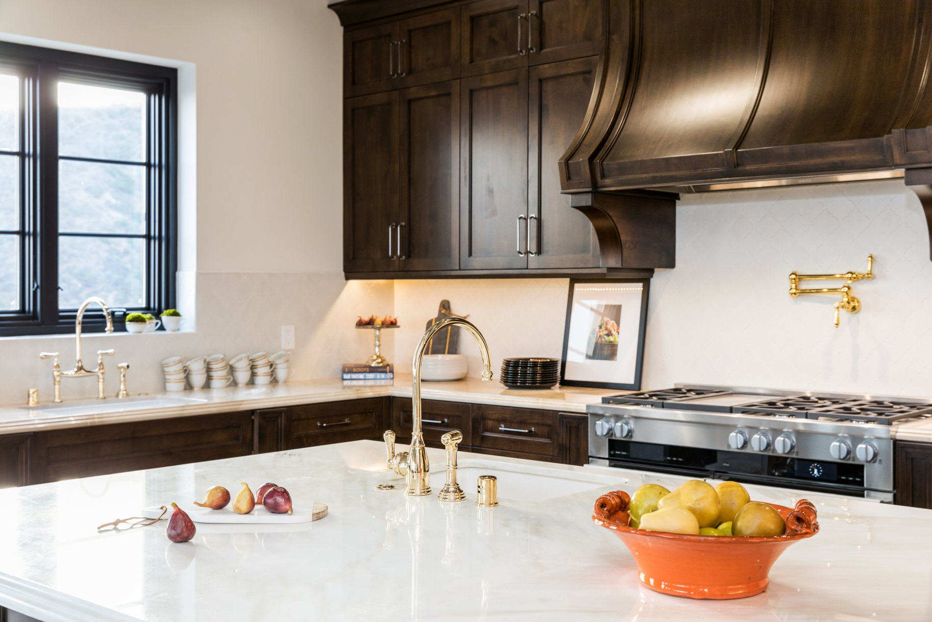 Large kitchen island with marble countertops and an undermount sink with gold faucet.