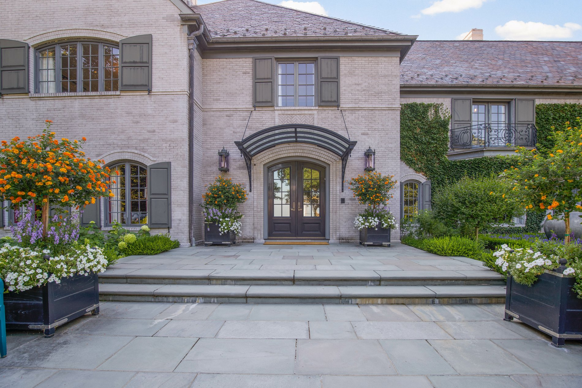 Brick home with an arched metal portico.