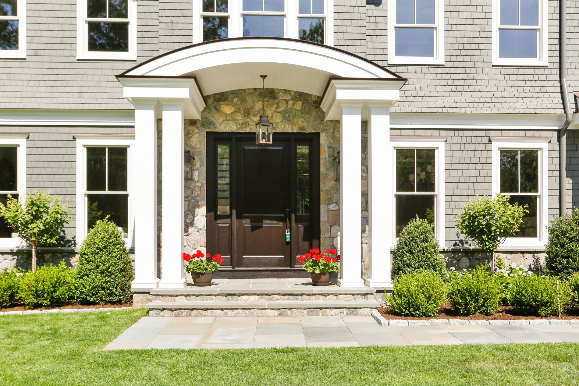 Beautiful arched portico with four square columns and a curved roof.