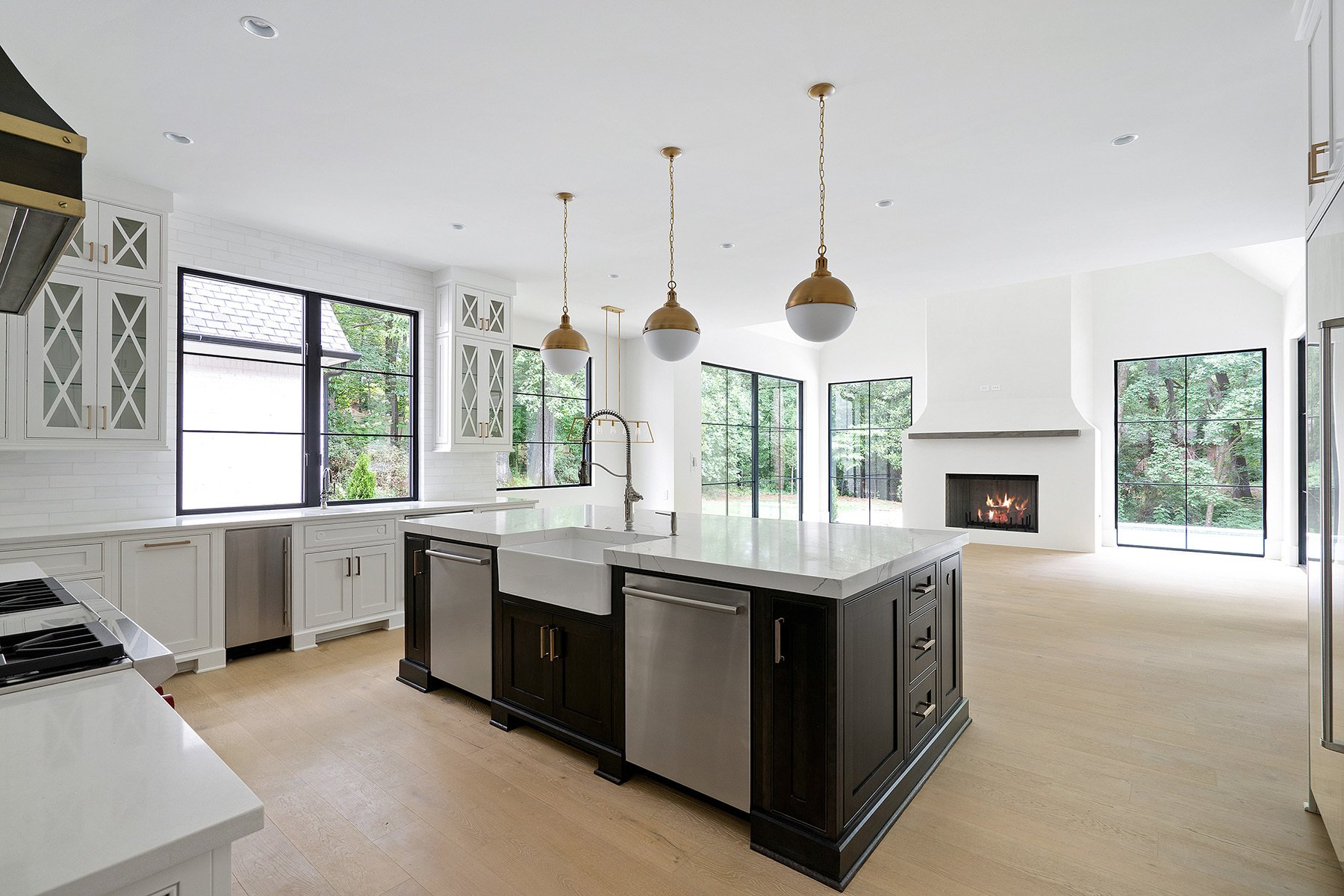 Beautiful black island with white cabinetry featuring a farmhouse sink and stainless steel appliances.