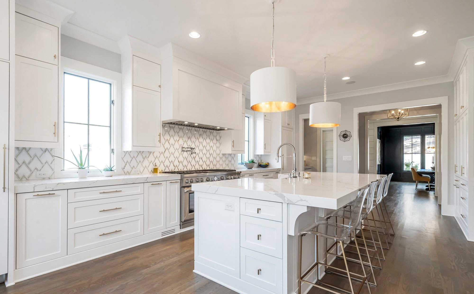 Beautiful white kitchen featuring a large island with seating, a farmhouse sink,storage and lots of seating.