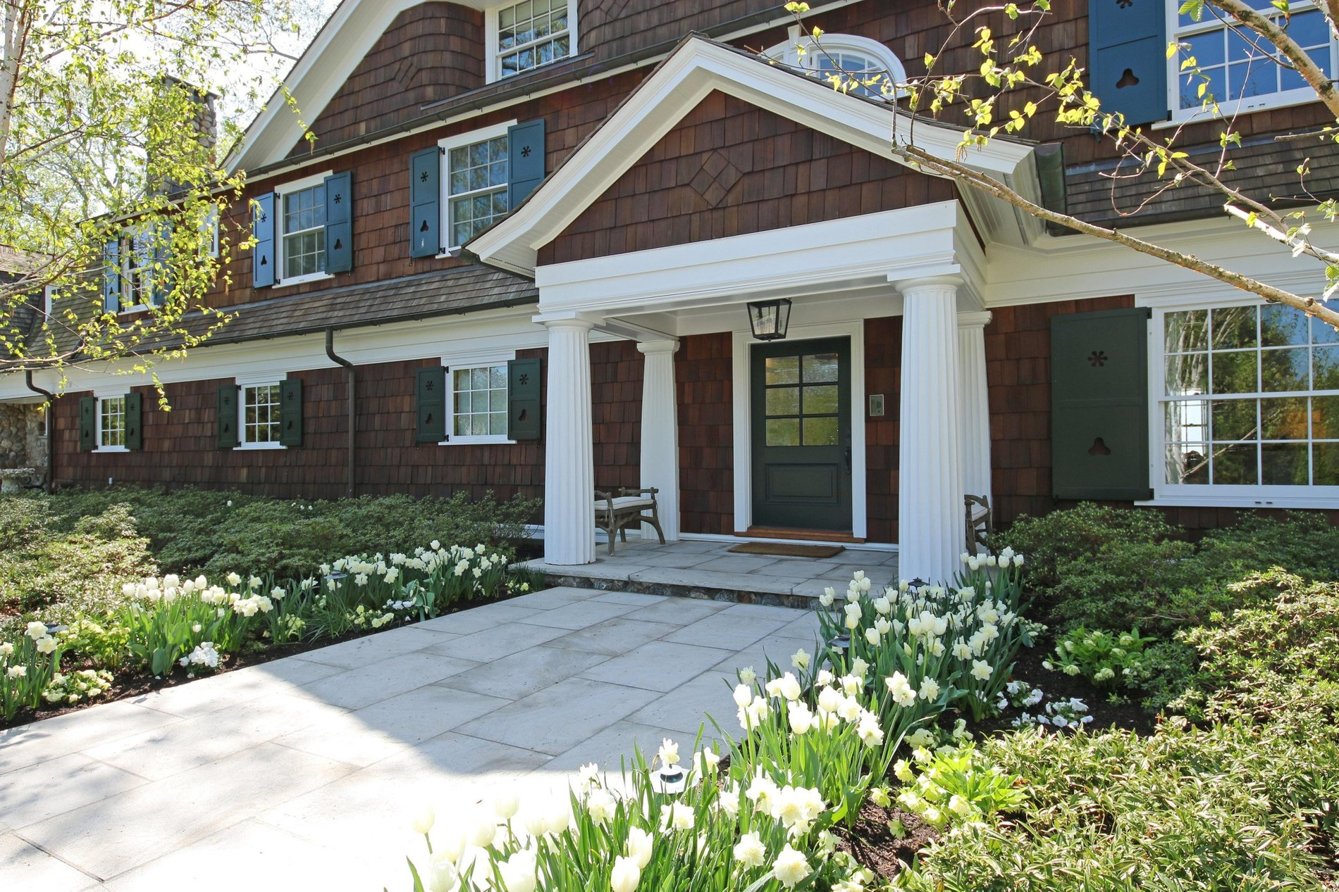 Shingle style a-frame portico with 4 round tapered and fluted columns.