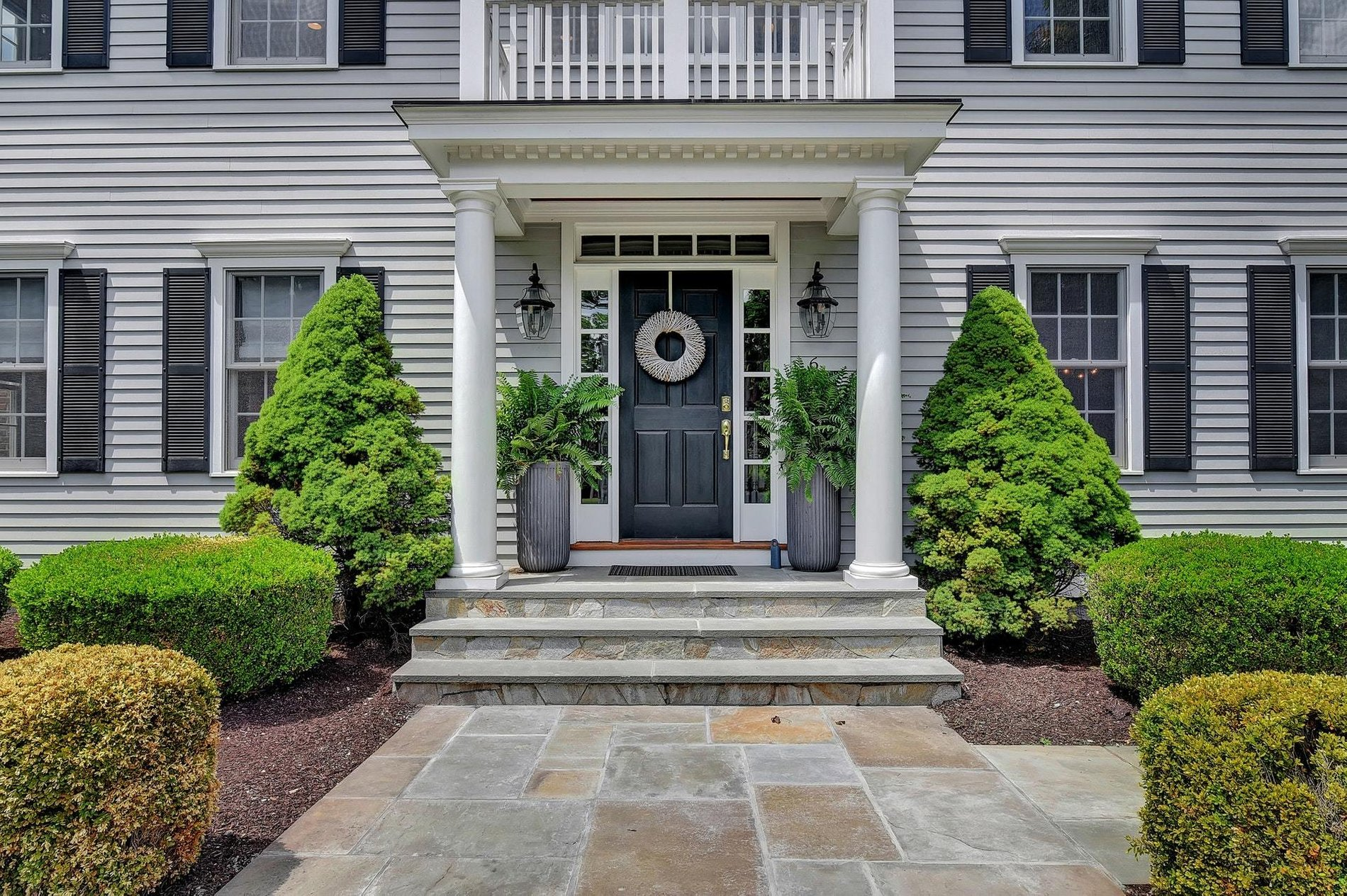 Classic portico design with a flat roof, round columns, railings and lots of trim and moldings. portico design ideas.