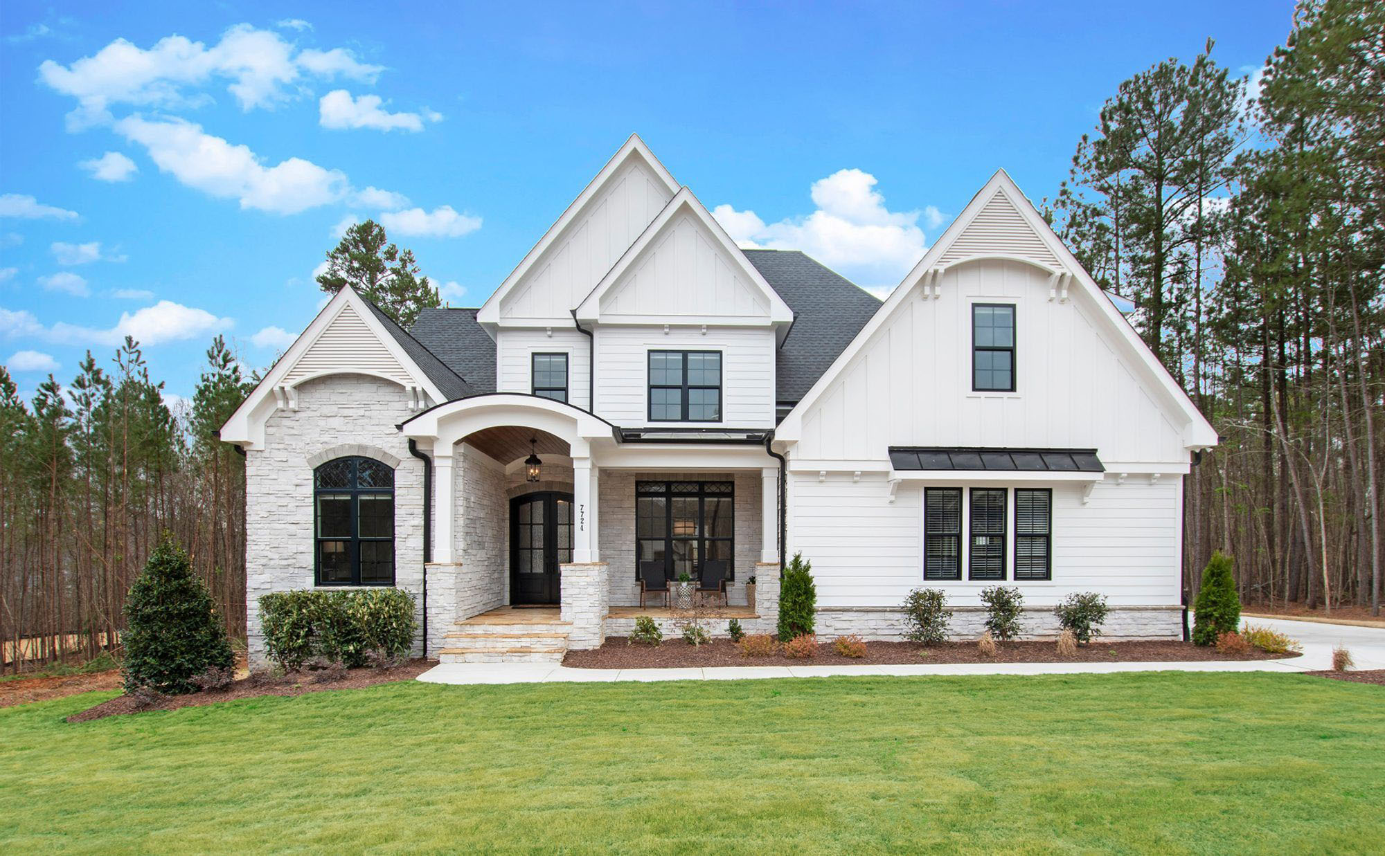 Beautiful modern farmhouse with an arched portico. Portico Designs.