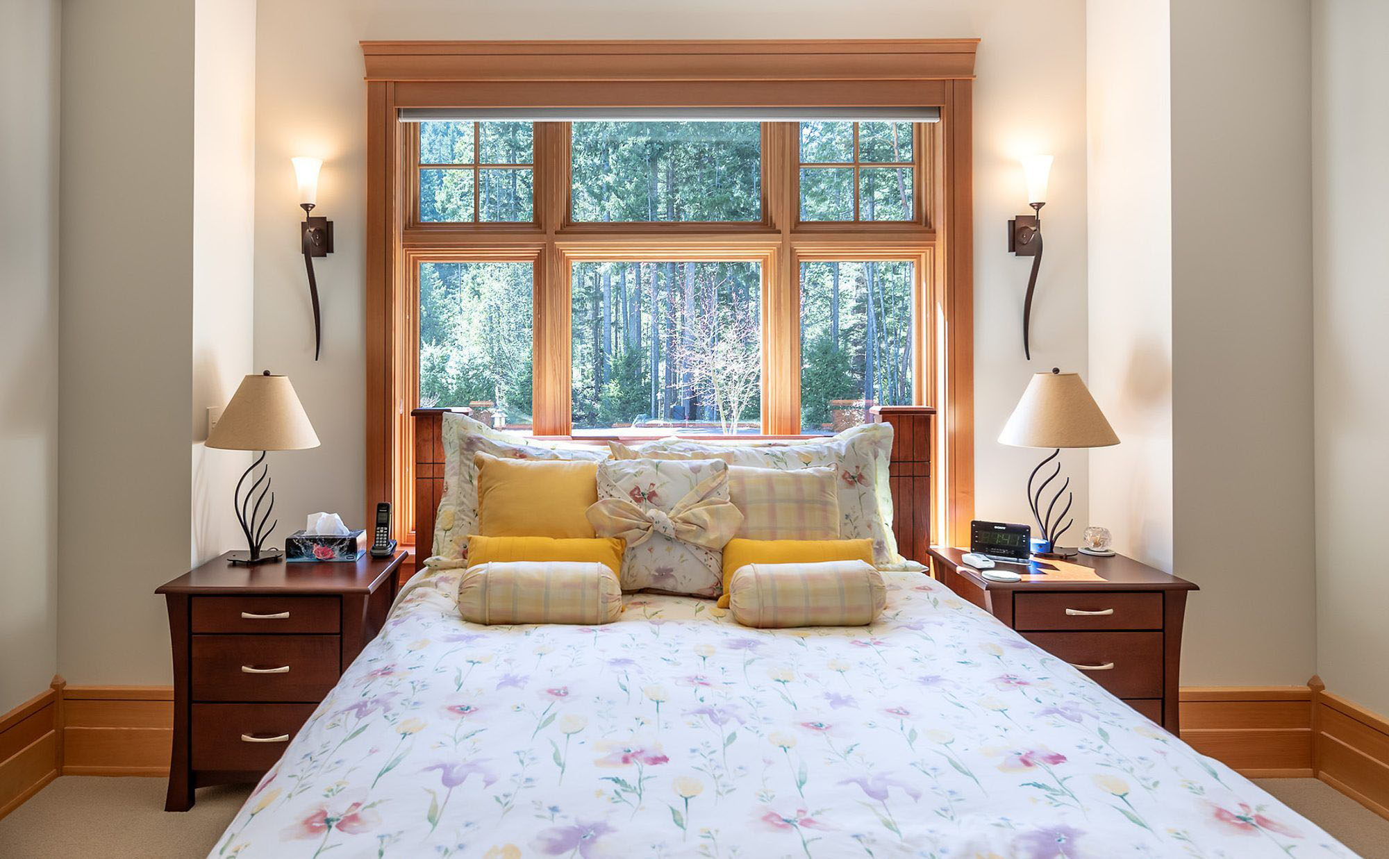 beautiful bed in front of a large window with wood bedside tables.