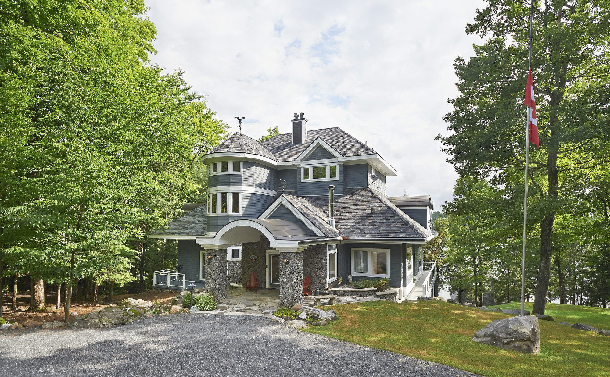 Beautiful custom waterfront blue home with an arched portico supported by stone columns.