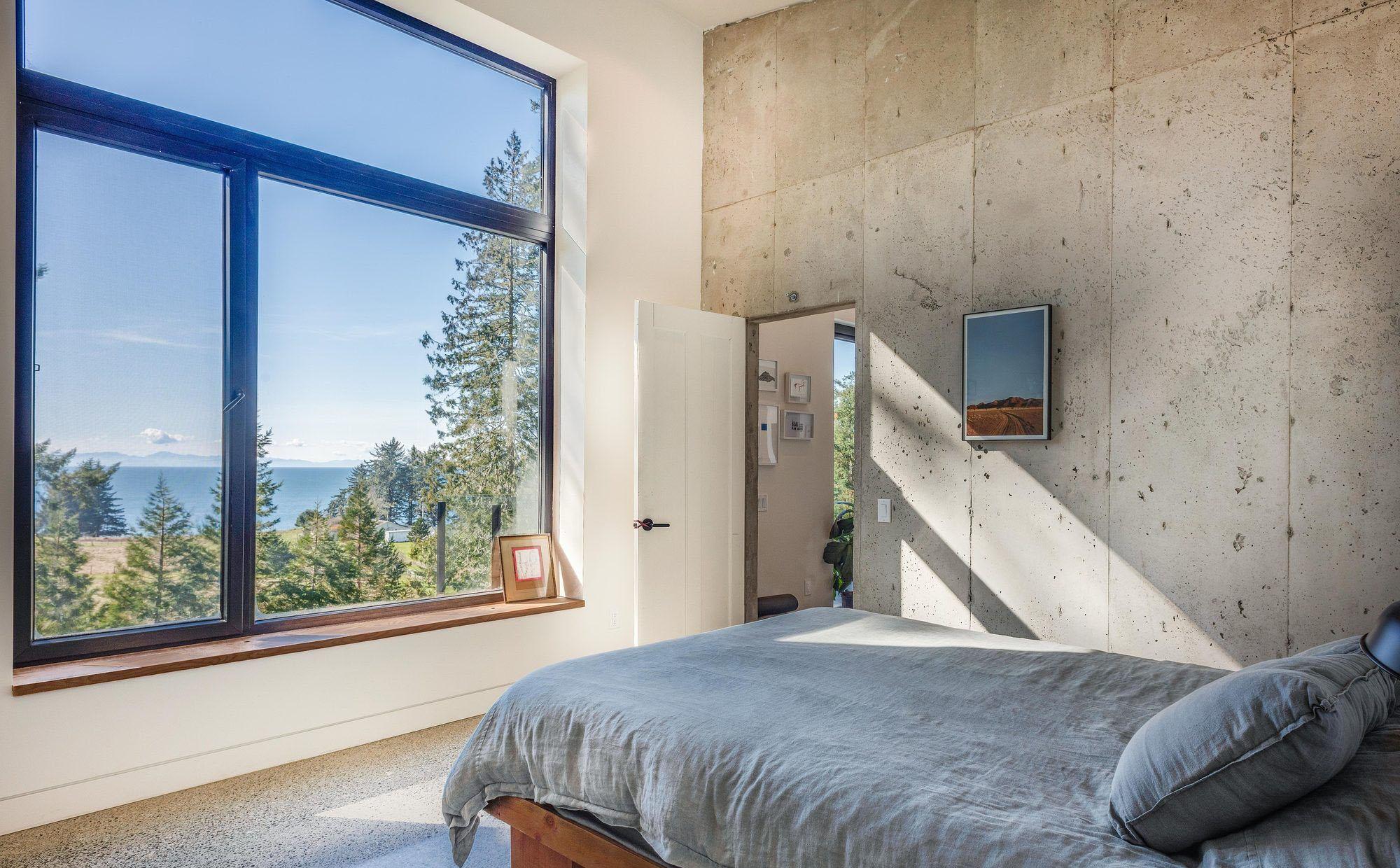 modern bedroom with concrete floors and walls. wood window shelf. minimalism.