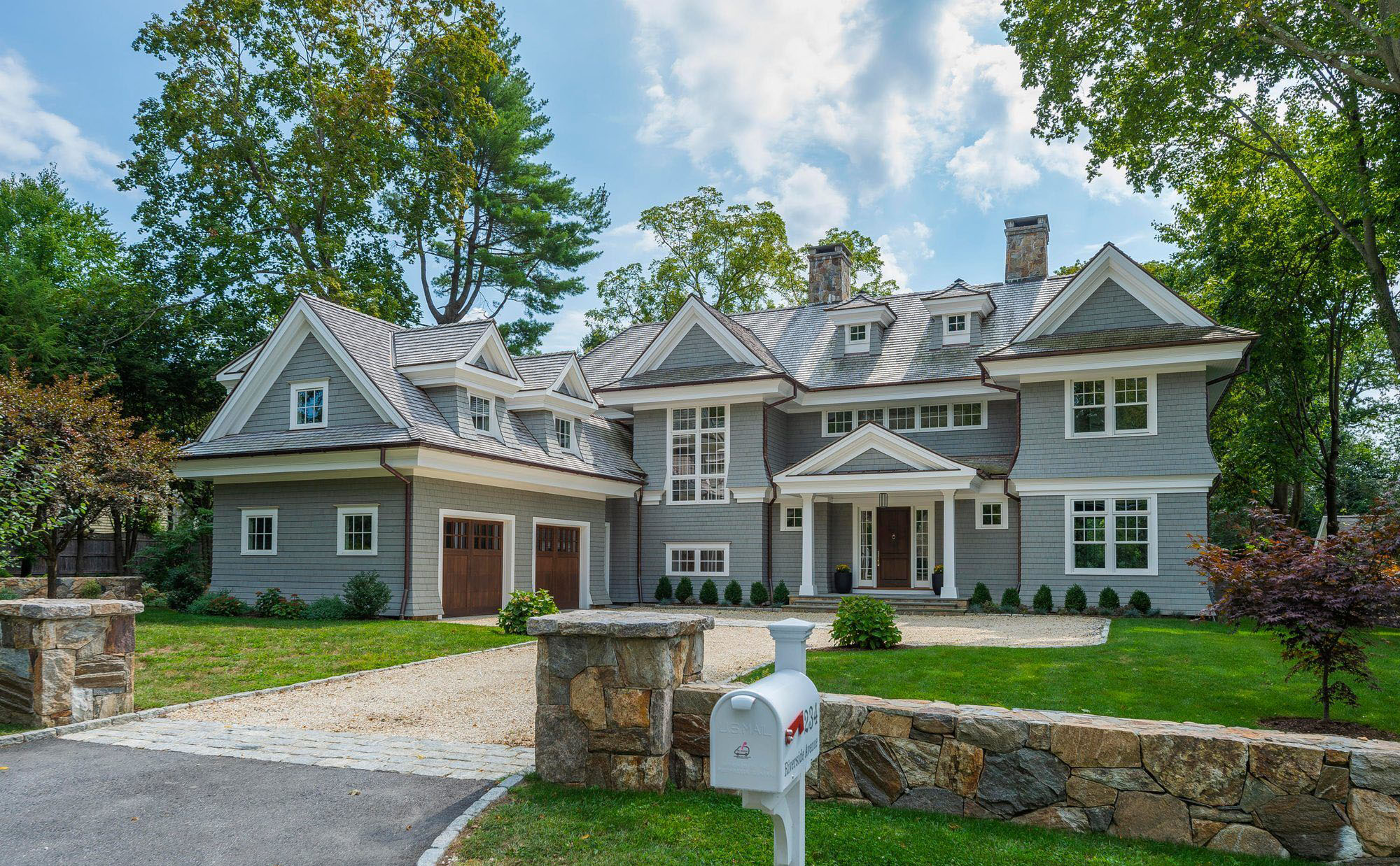 Beautiful shingle style new home featuring grey siding, stained wood doors and white trim.