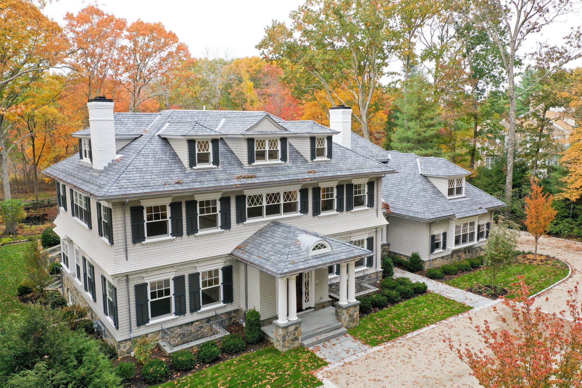 Beautiful custom home with a hip roof portico supported by 4 round columns & stone bases.