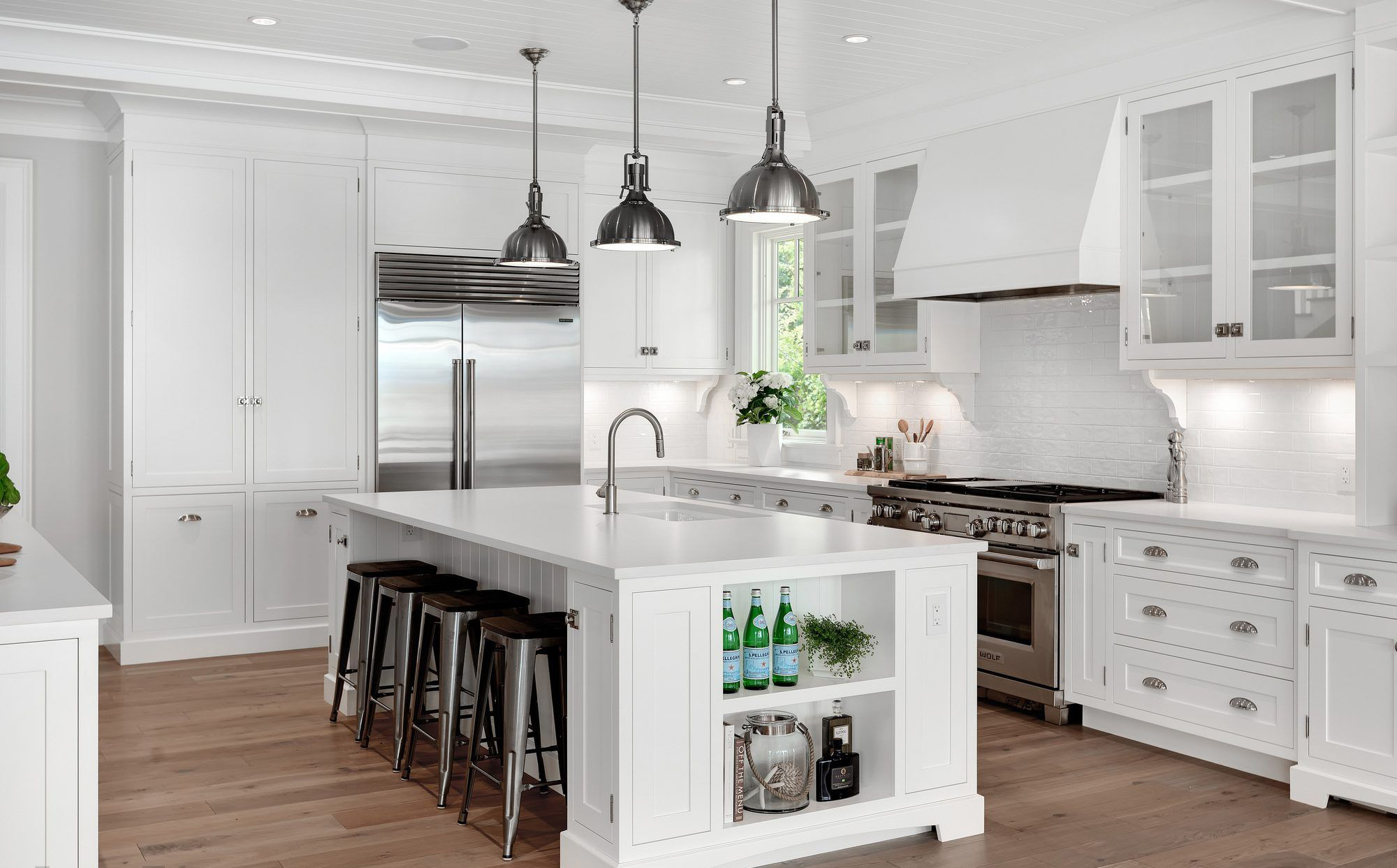 Beautiful white kitchen island with a white countertop and lots of built in storage.