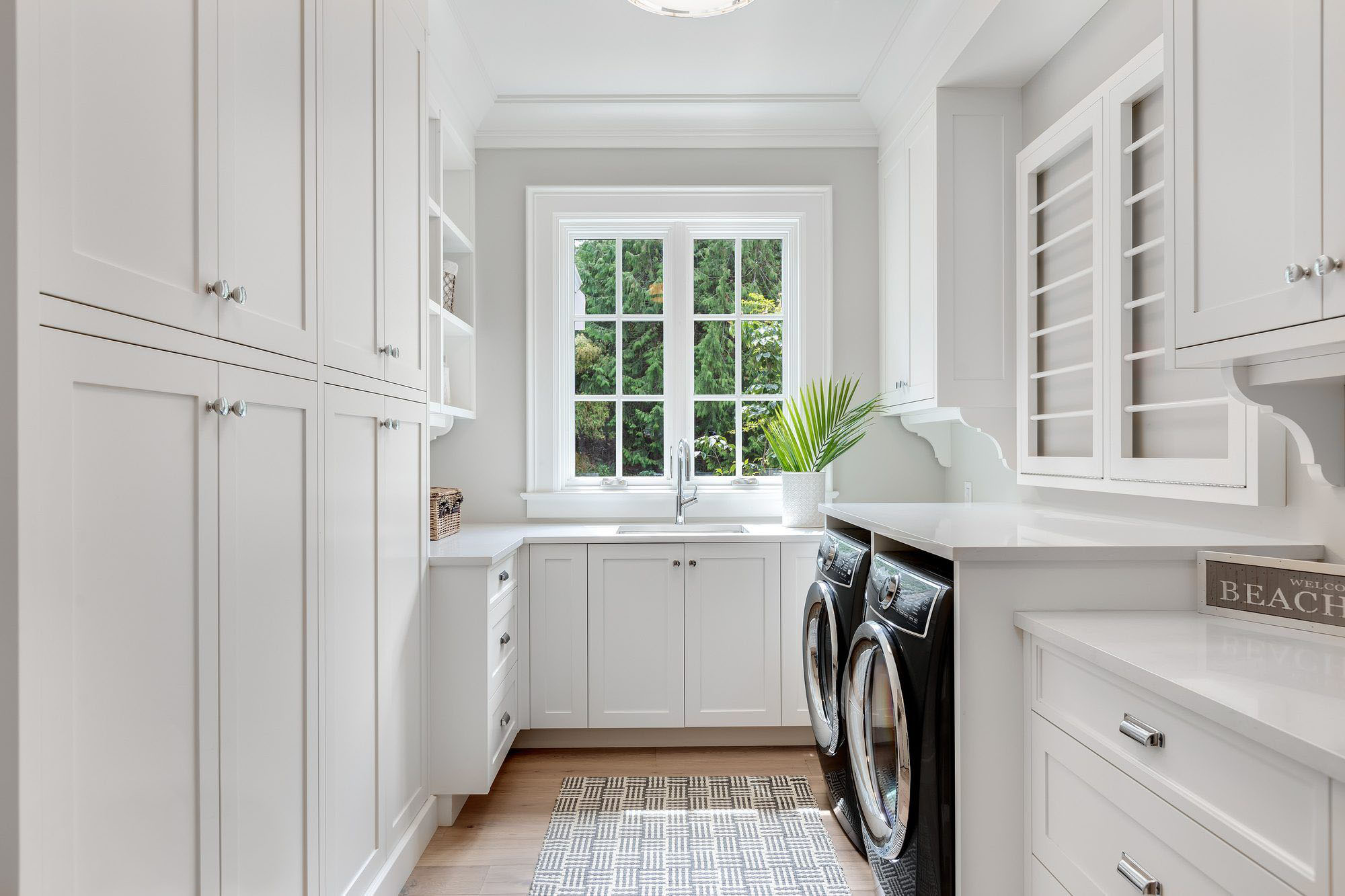 Beautiful light and bright laundry room with white cabinets, pale wood floors, a sink, folding table, countertops and a plant.