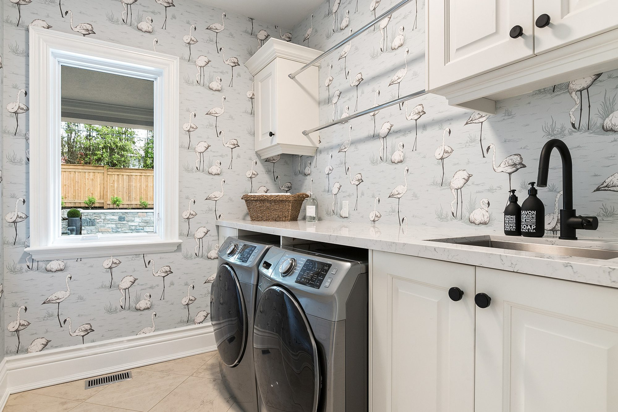 White laundry room cabinetry with black hardware and matching black faucet.