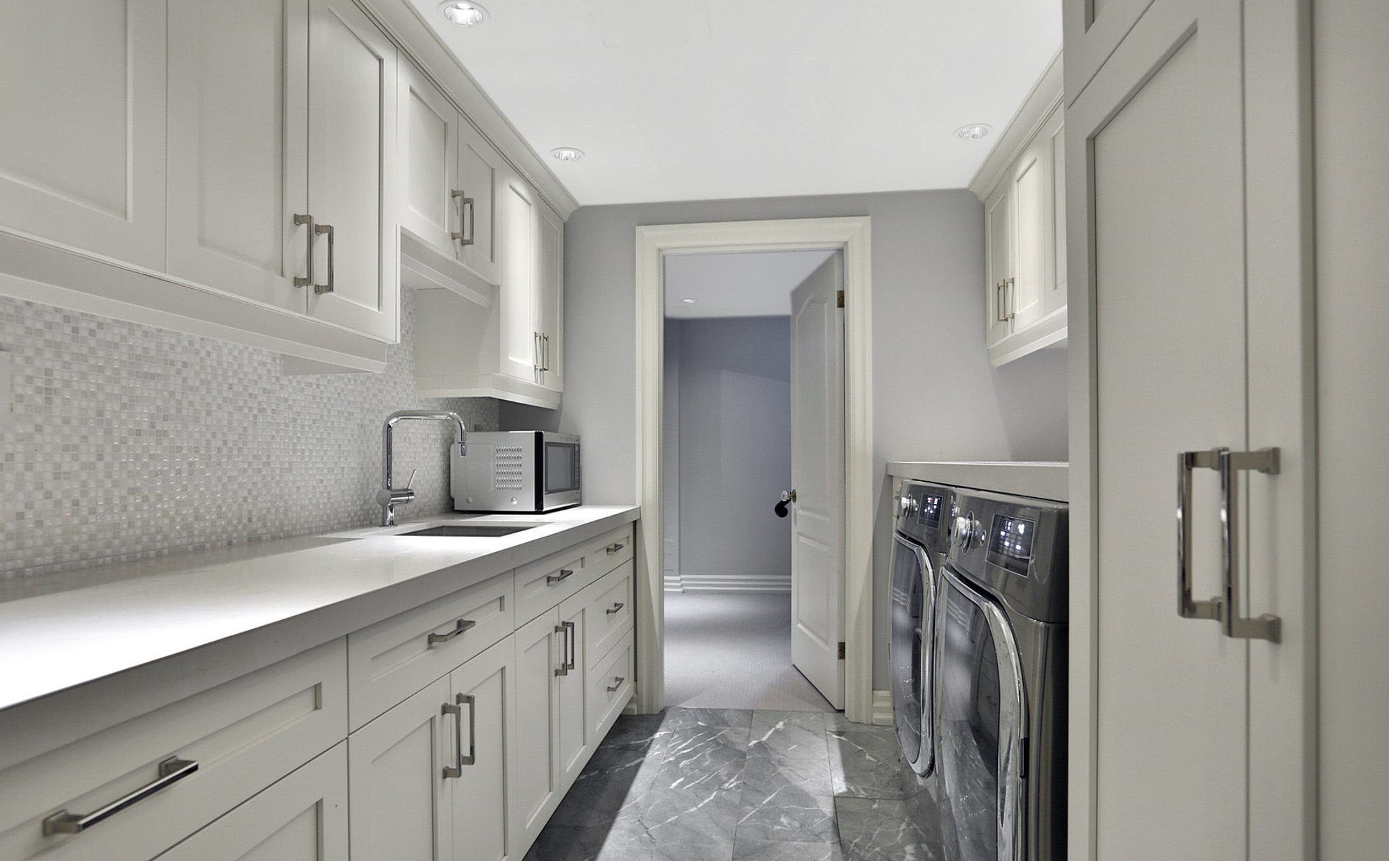 Laundry room with a grey and white backsplash made from small 1/2 inch tiles.