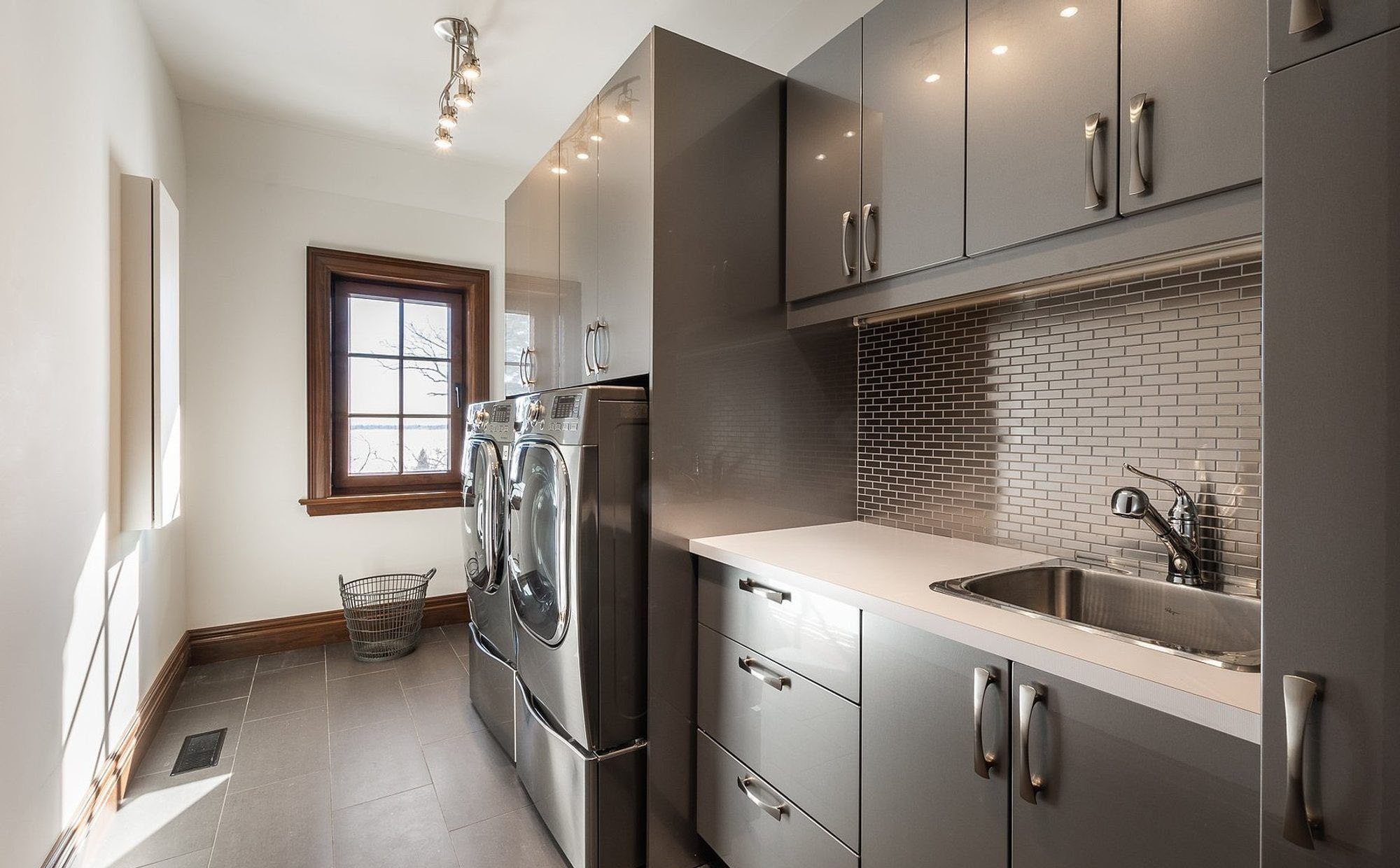Steel colored laundry room with shiny grey cabinetry, grey tile floors, grey washer/dryer and a stainless steel sink.
